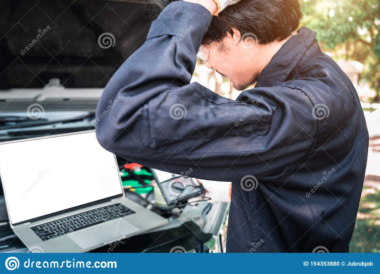 Mechanic Using Laptop While Examining Car Engine, pointing in blank screen