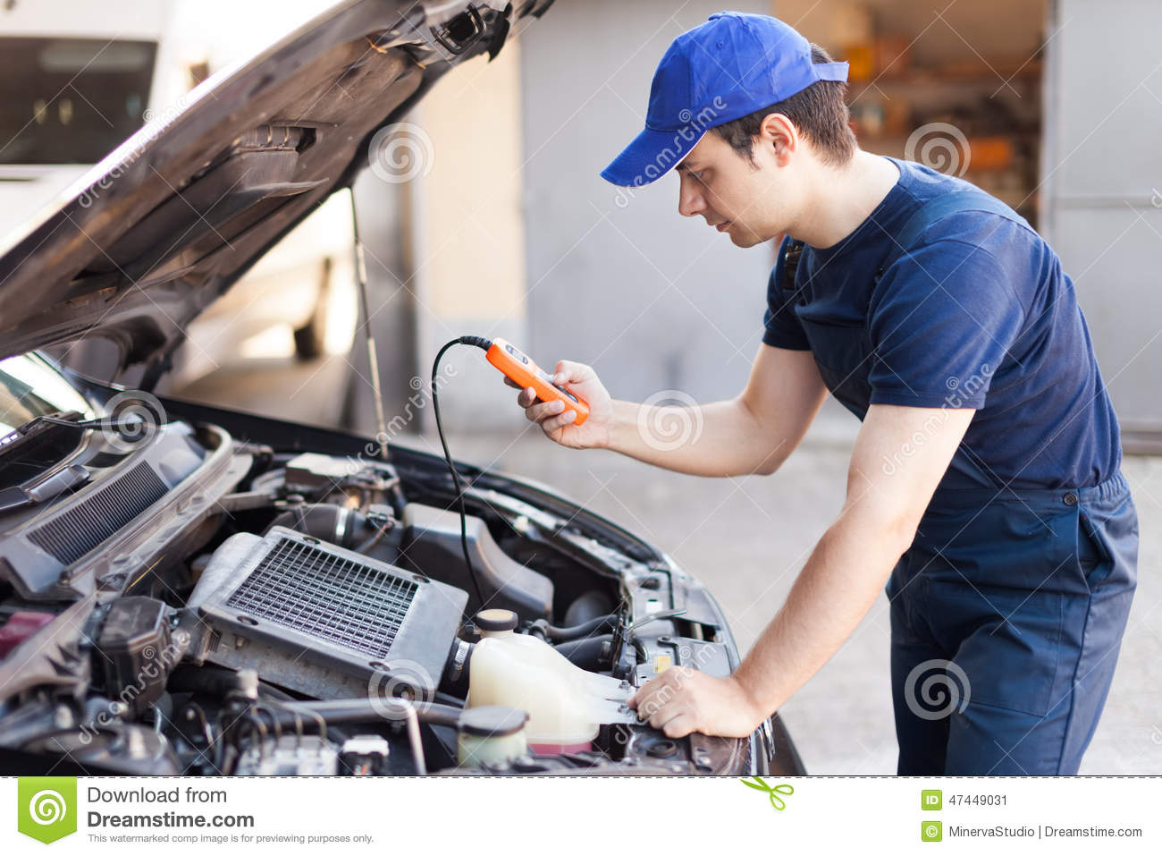 Mechanic using a tester on a car engine