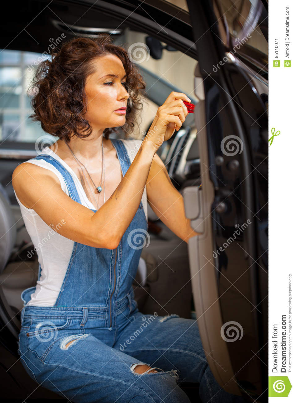Mechanic woman in a blue overalls repair with a screwdriver the