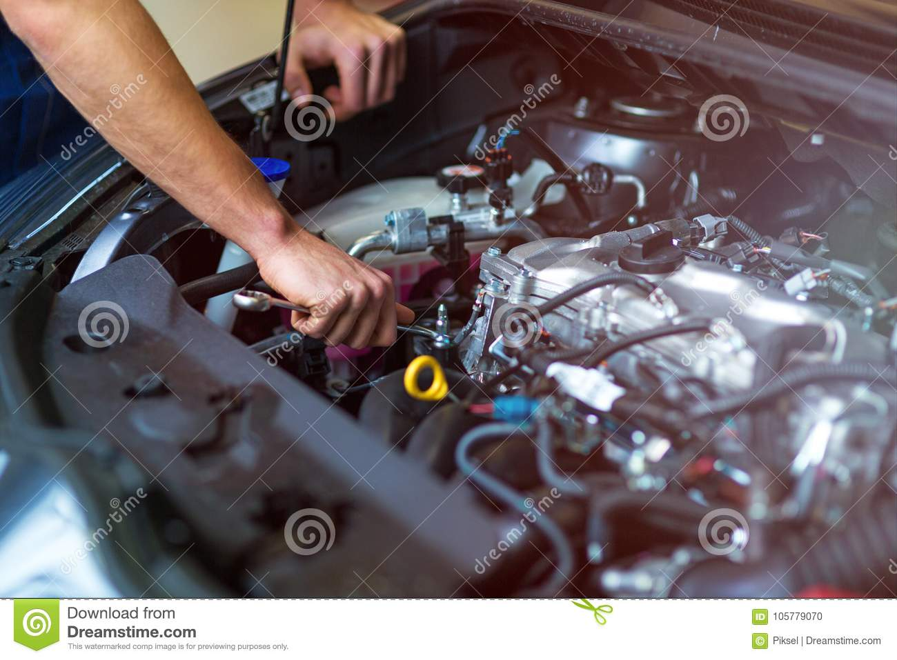 Mechanic working on car engine in auto repair shop
