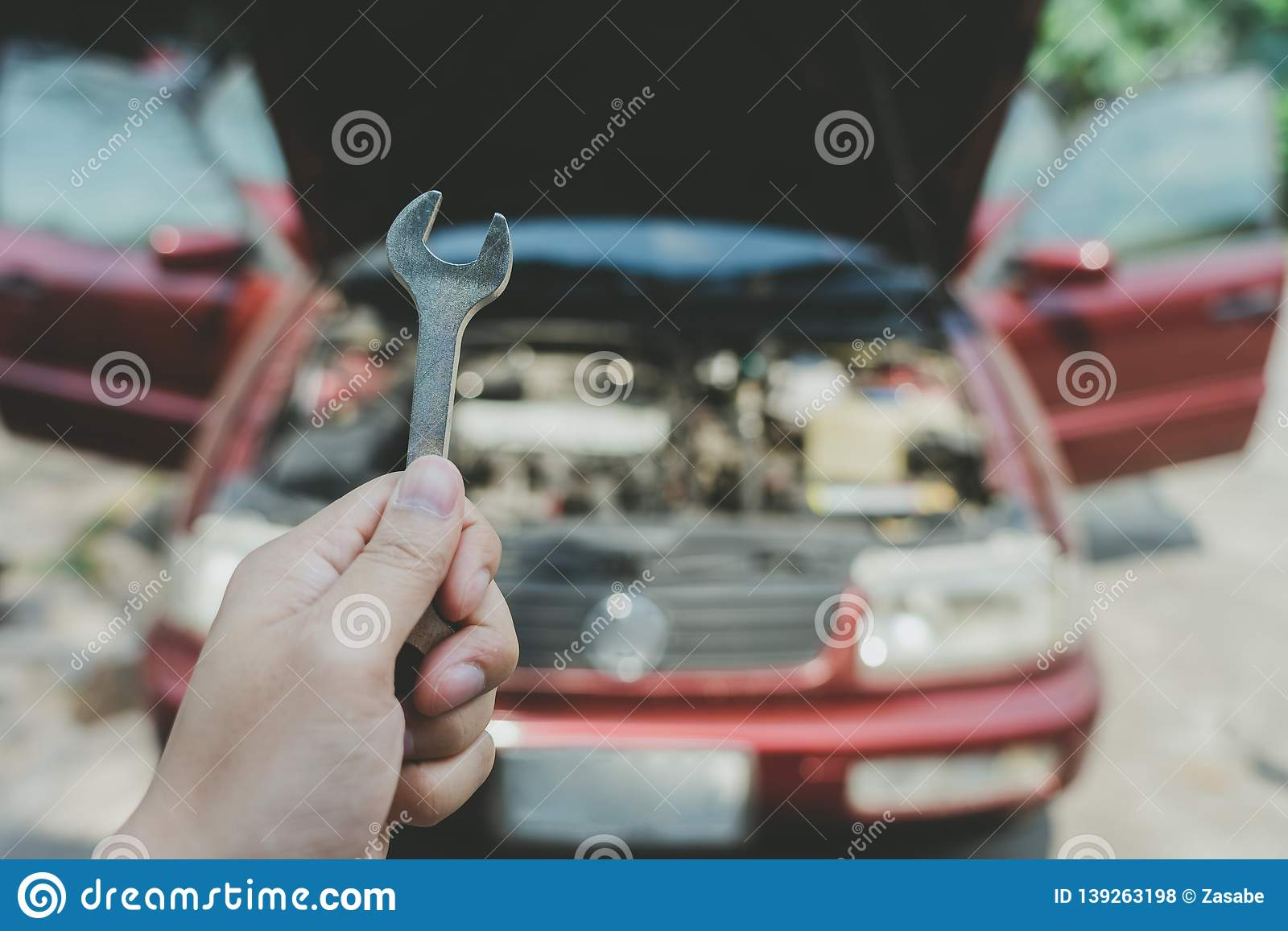 Mechanical engineer hands open the car skirt to check the oil level of the car. The concept of engine maintenance Travel safely