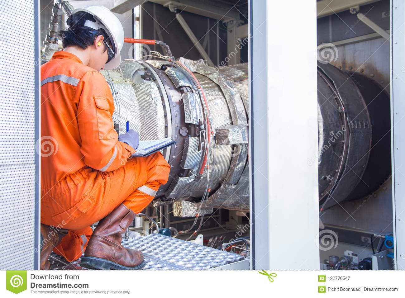 Mechanical engineering inspector checking gas turbine engine inside package enclosure .