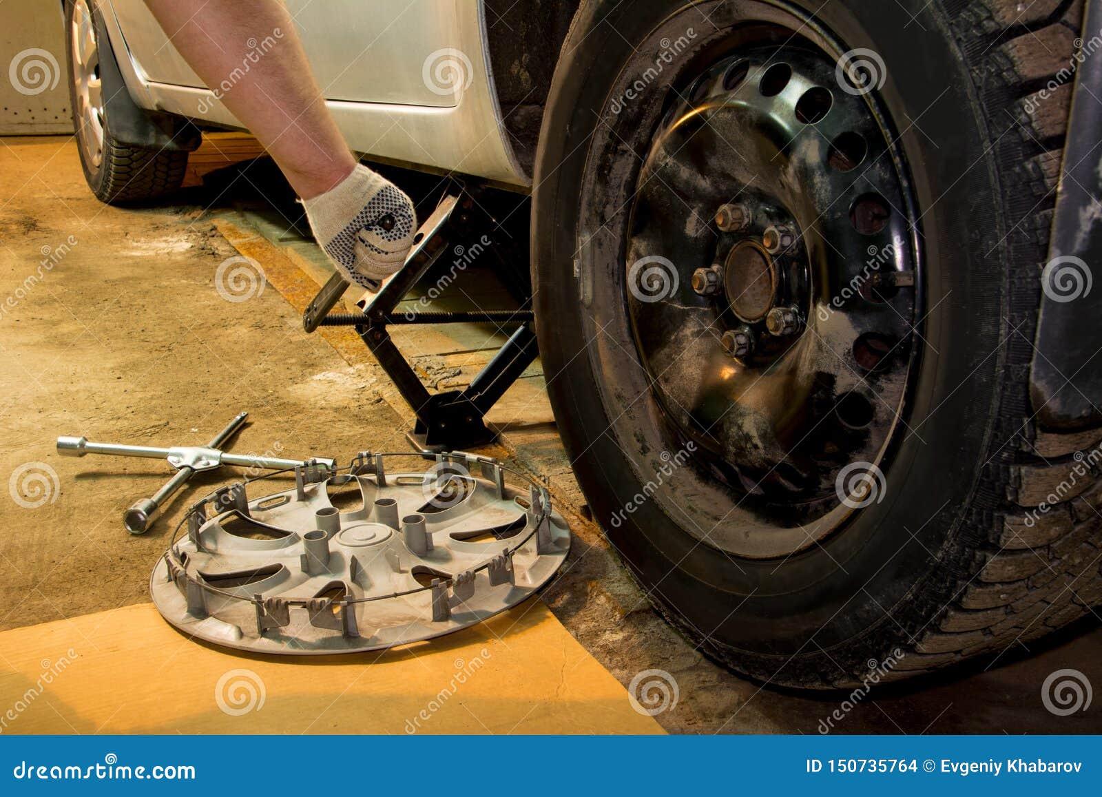 Mechanician veranderend autowiel in garage Mens die band ruilen De banddienst