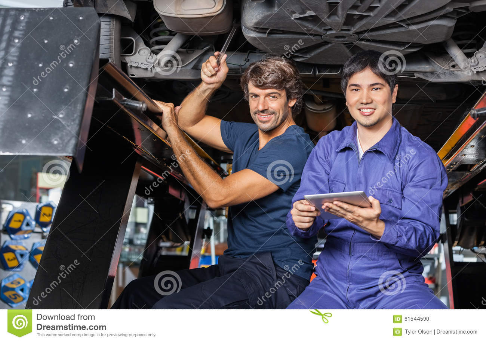 Mechanicy Z Cyfrowej pastylką Pracuje Pod Podnoszący