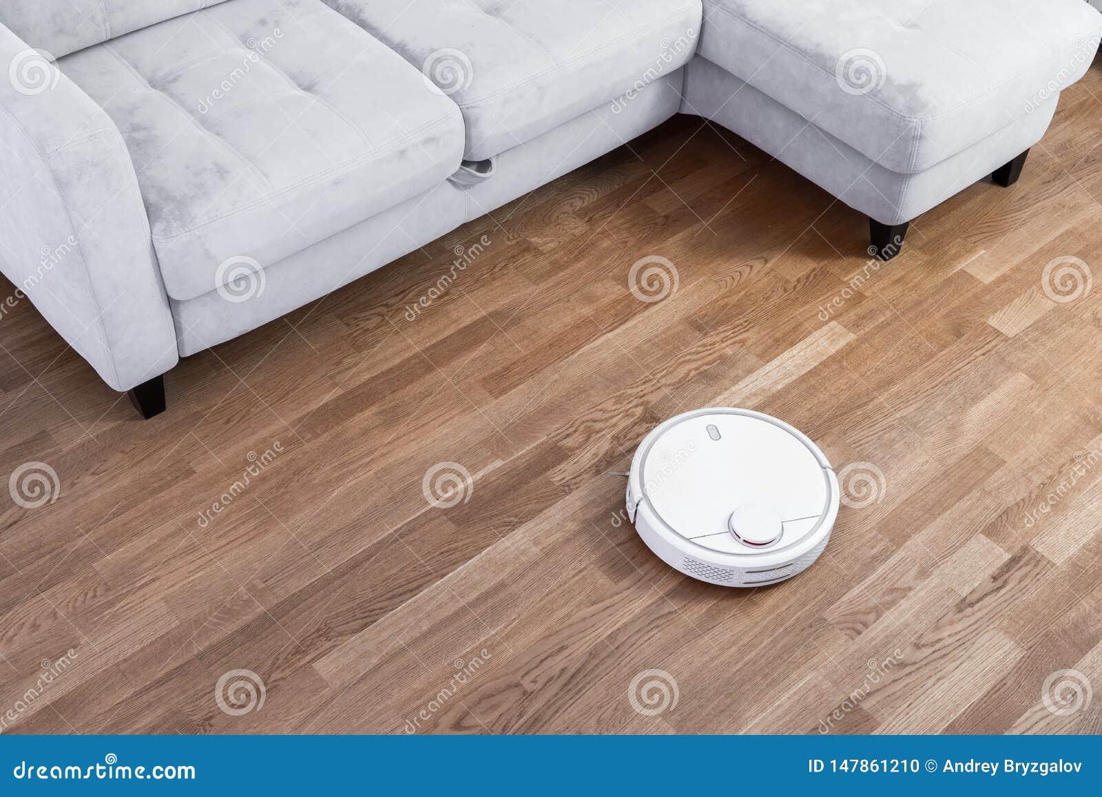 Mechaniczni pr??niowi czy?ci bieg blisko kanapy na laminat pod?odze Robot kontroluj?cy g?osem dowodzi kierowa? cleaning Nowo?ytny
