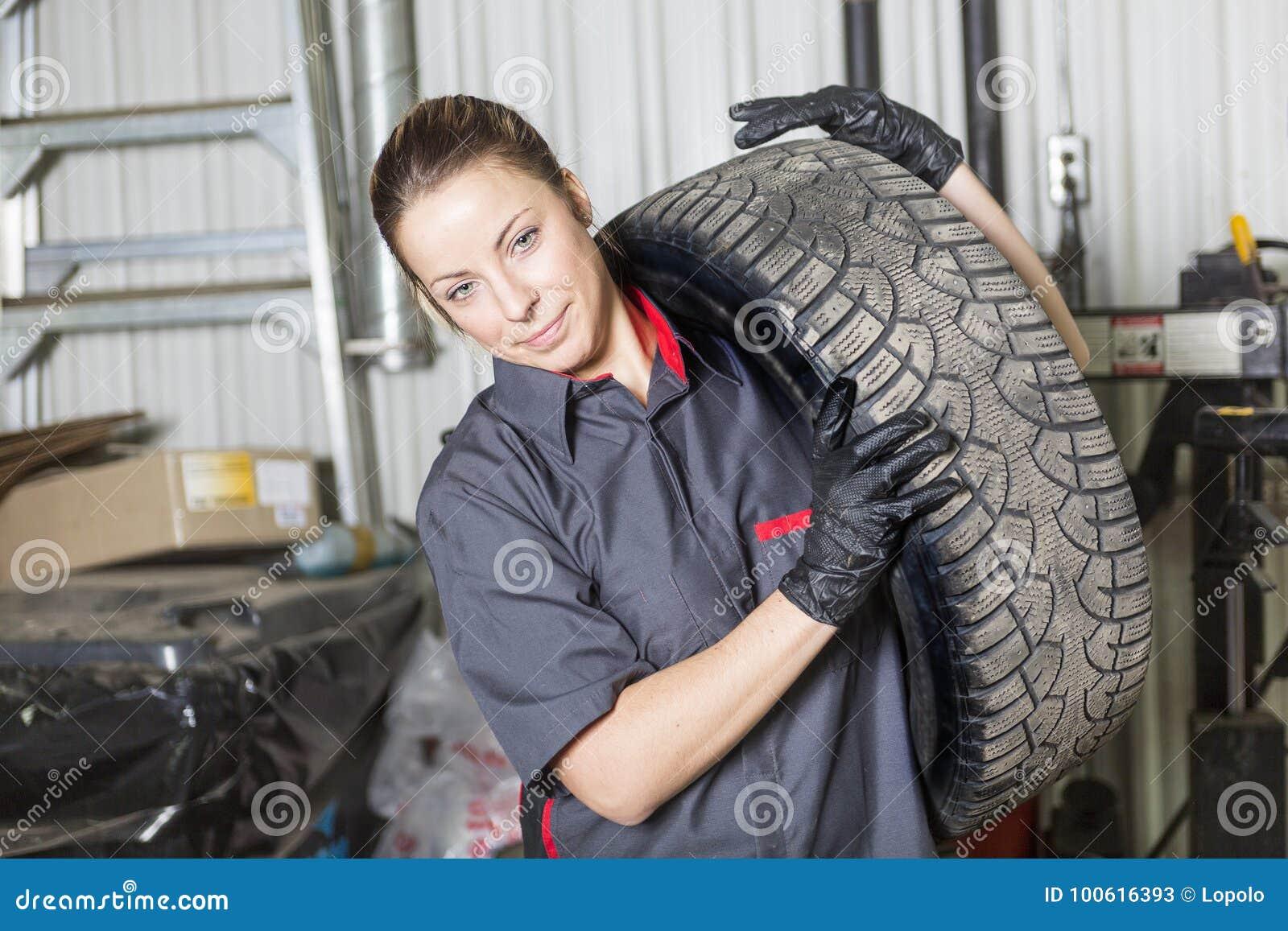 Mechanik kobieta pracuje na samochodzie w jego sklepie