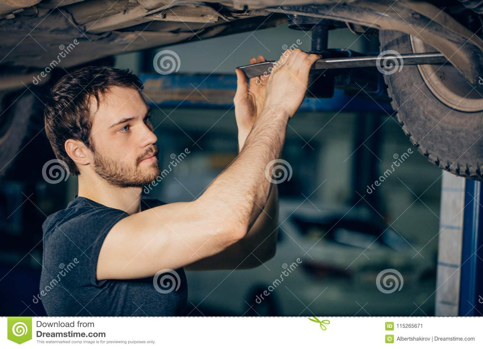 Mechanik pod samochodem w garaż examing oponie i technicznym warunku