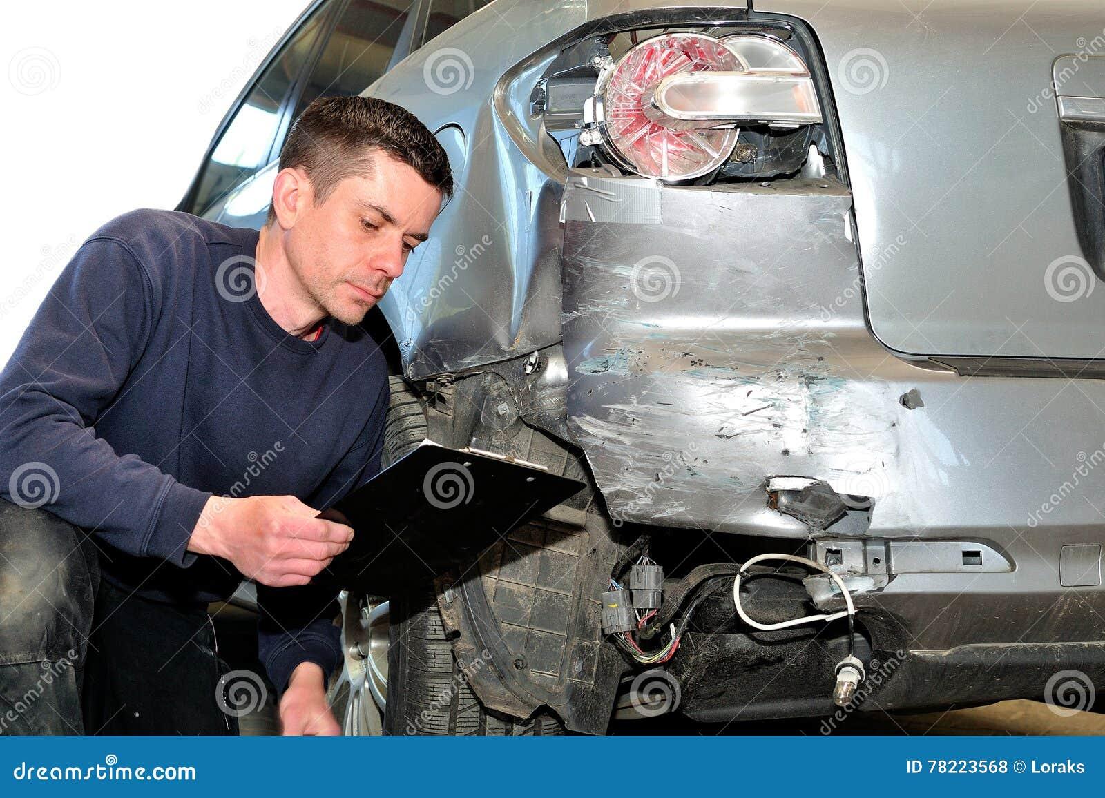 Mechanik sprawdza samochodowego ciało przy auto remontowego sklepu stacją obsługi