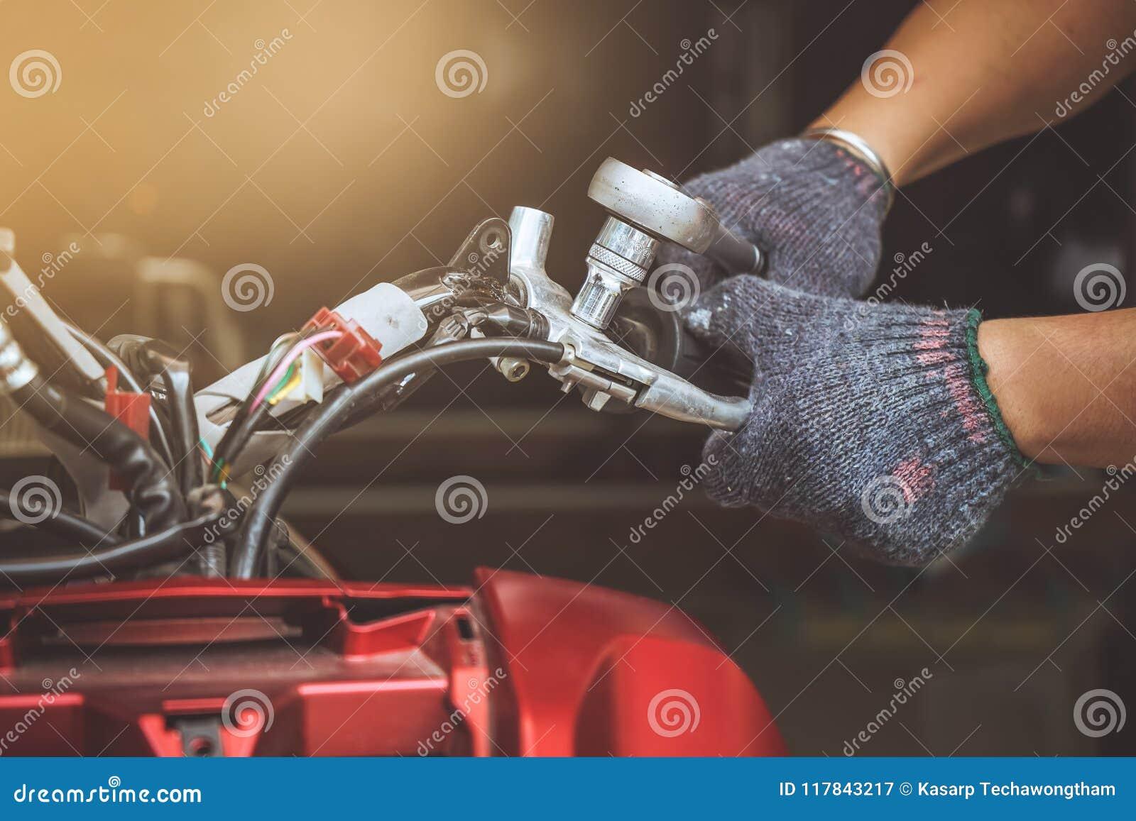 Mechanika mężczyzna używa wyrwanie Naprawiać motocykl lub utrzymywać przy
