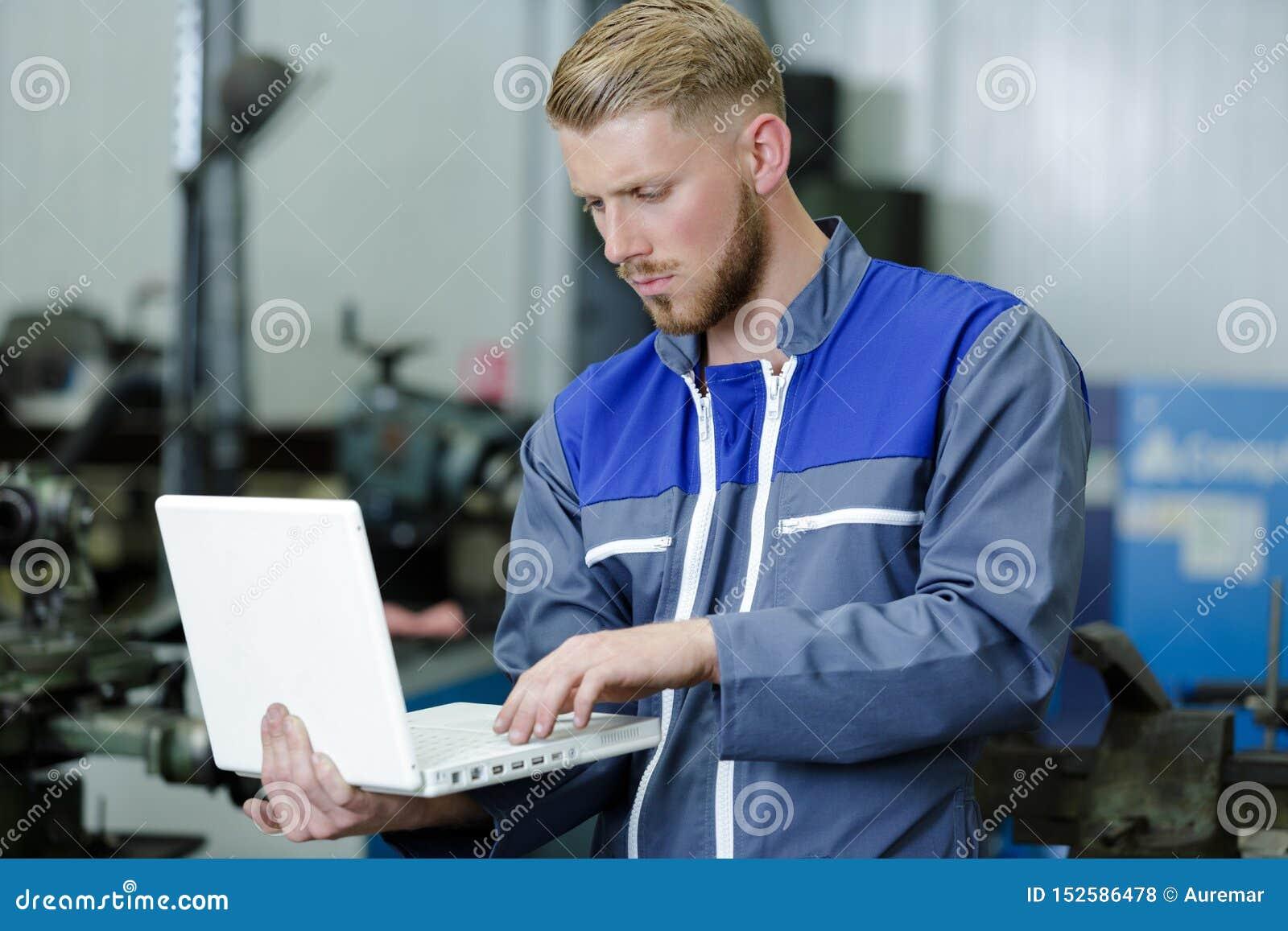 Mechaniker, der Laptop f?r die Pr?fung des Automotors verwendet