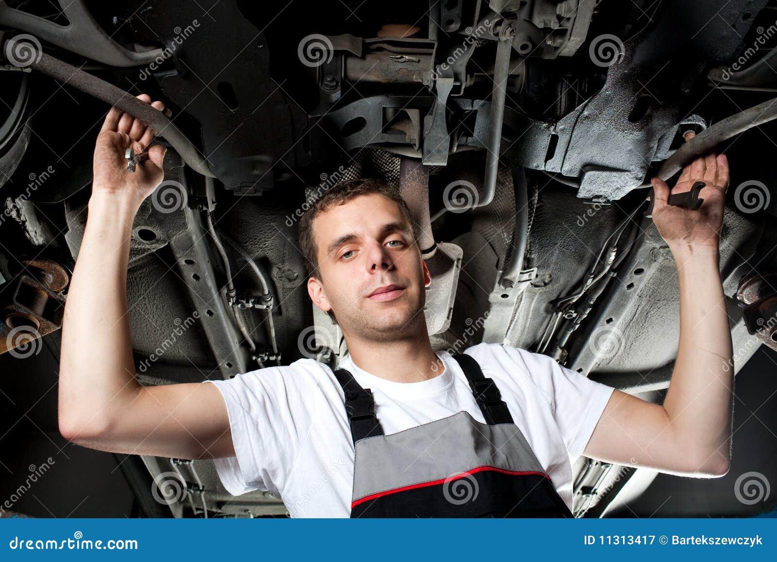 Mechaniker, der unter Auto in der Uniform mit Schlüssel arbeitet