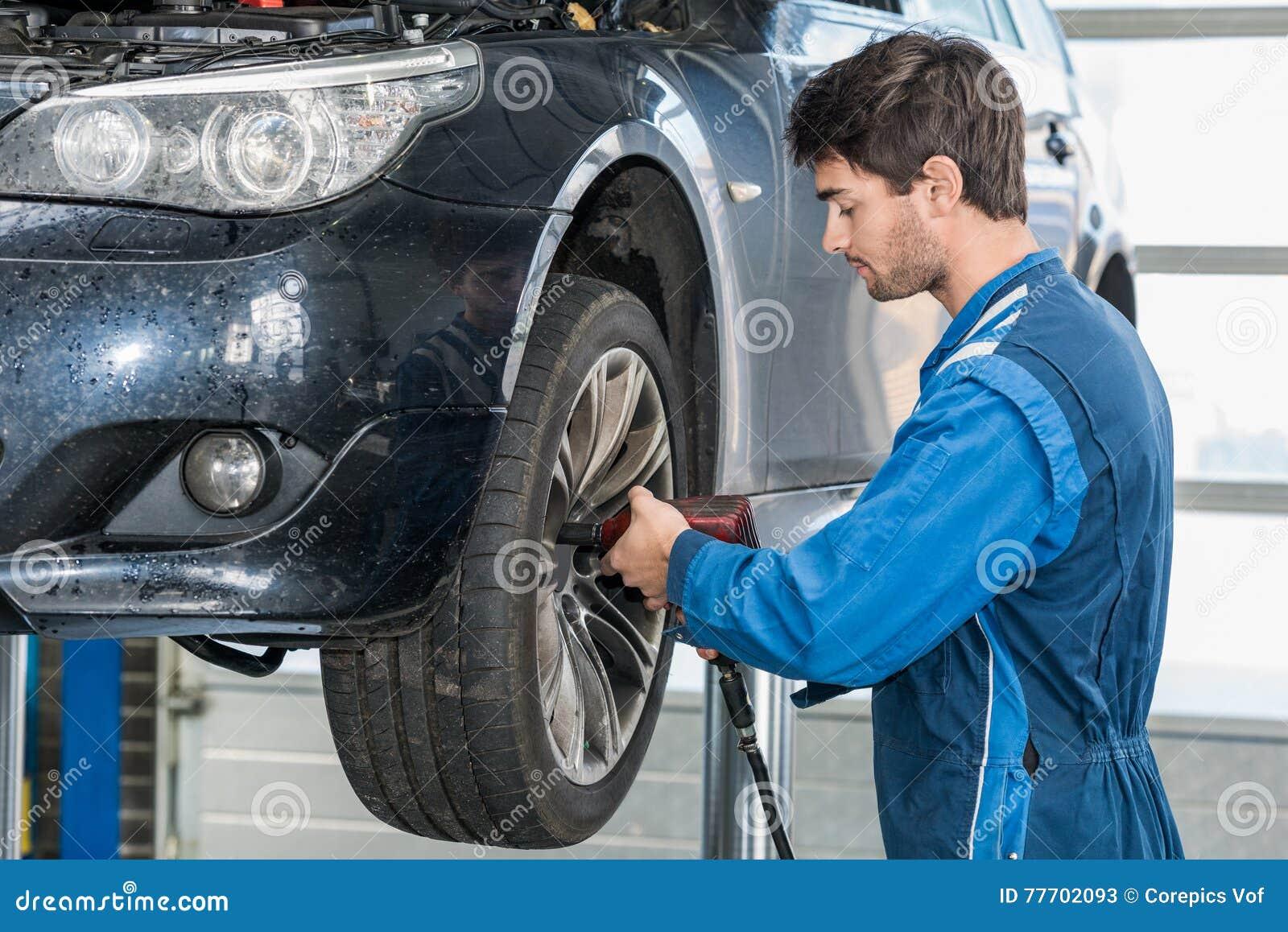 Mechaniker Using Pneumatic Wrench, zum des Autoreifens zu reparieren
