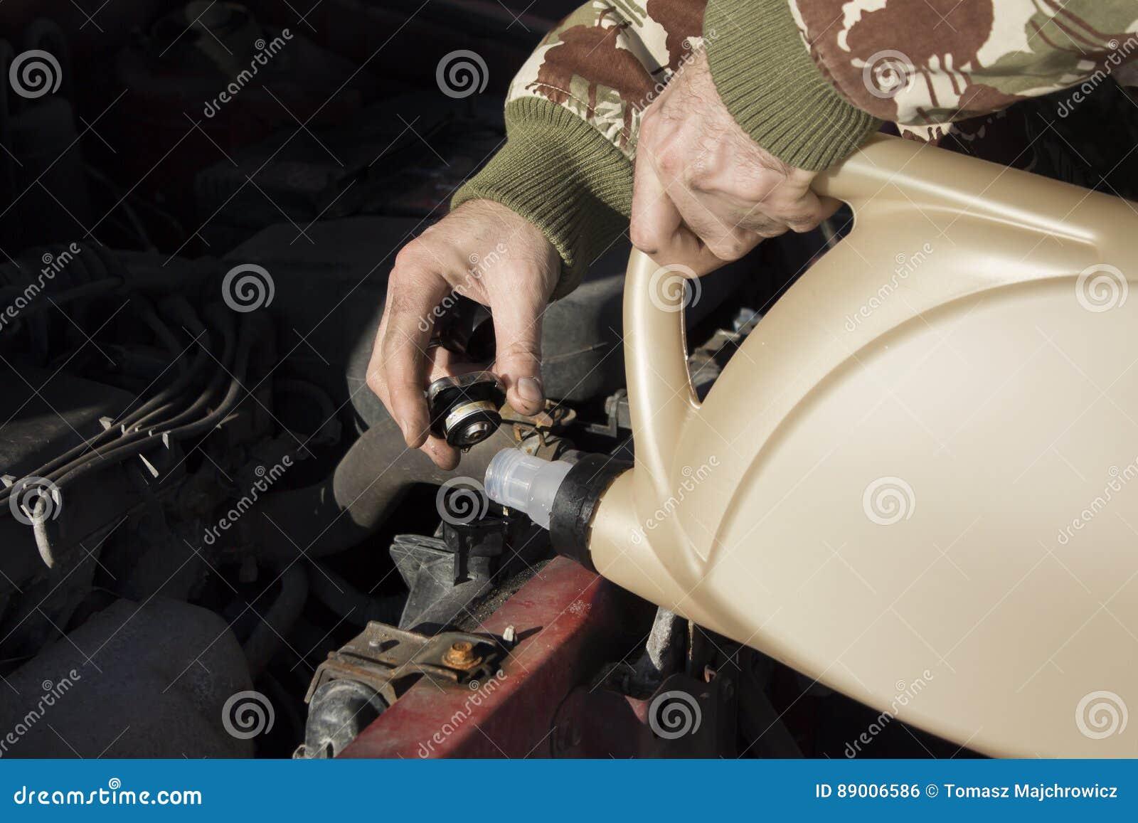 Mechanisch gietend koelmiddel aan de radiator Het mannetje maakt een lijst van het koelmiddel in het koelsysteem