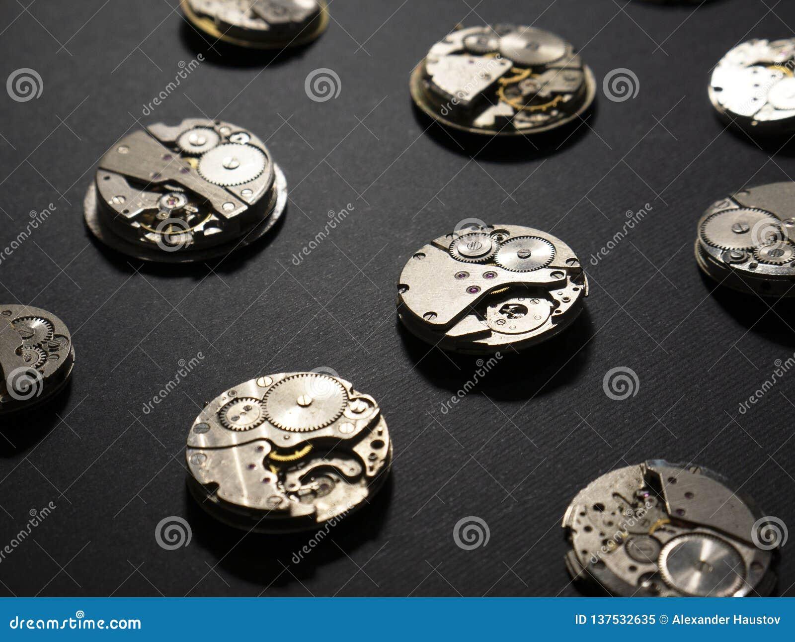 Mechanizmy zegarki i ich części na czarnym tle