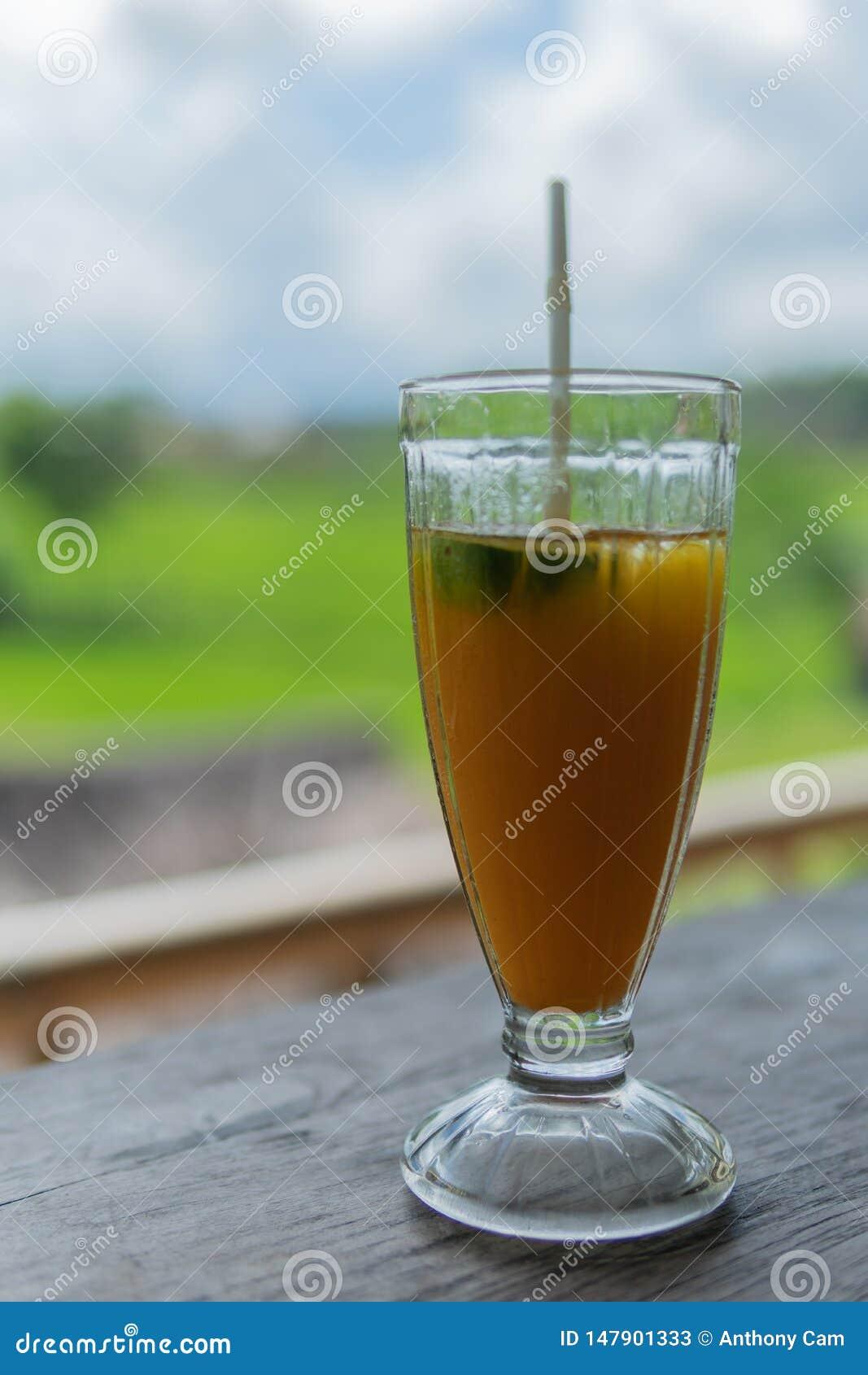 Med is drink för mangopapayabanan med risfält i bakgrunden