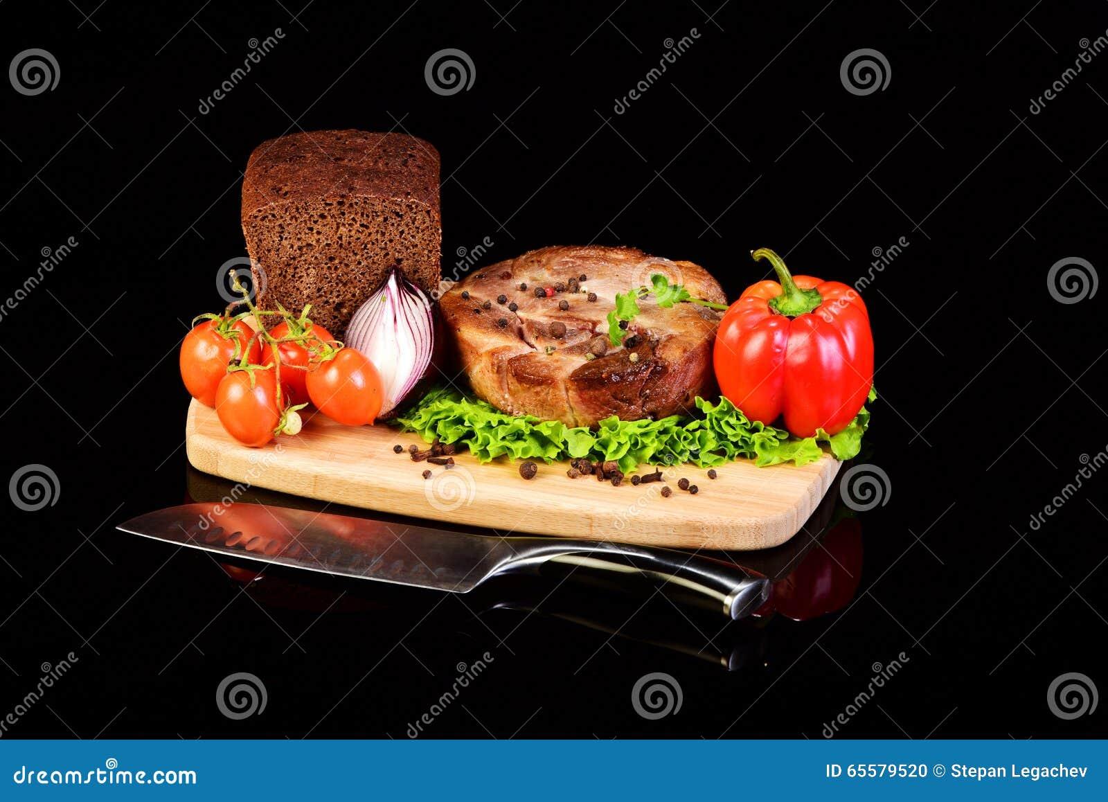 Medalhão e vegetais da carne em uma placa de pão