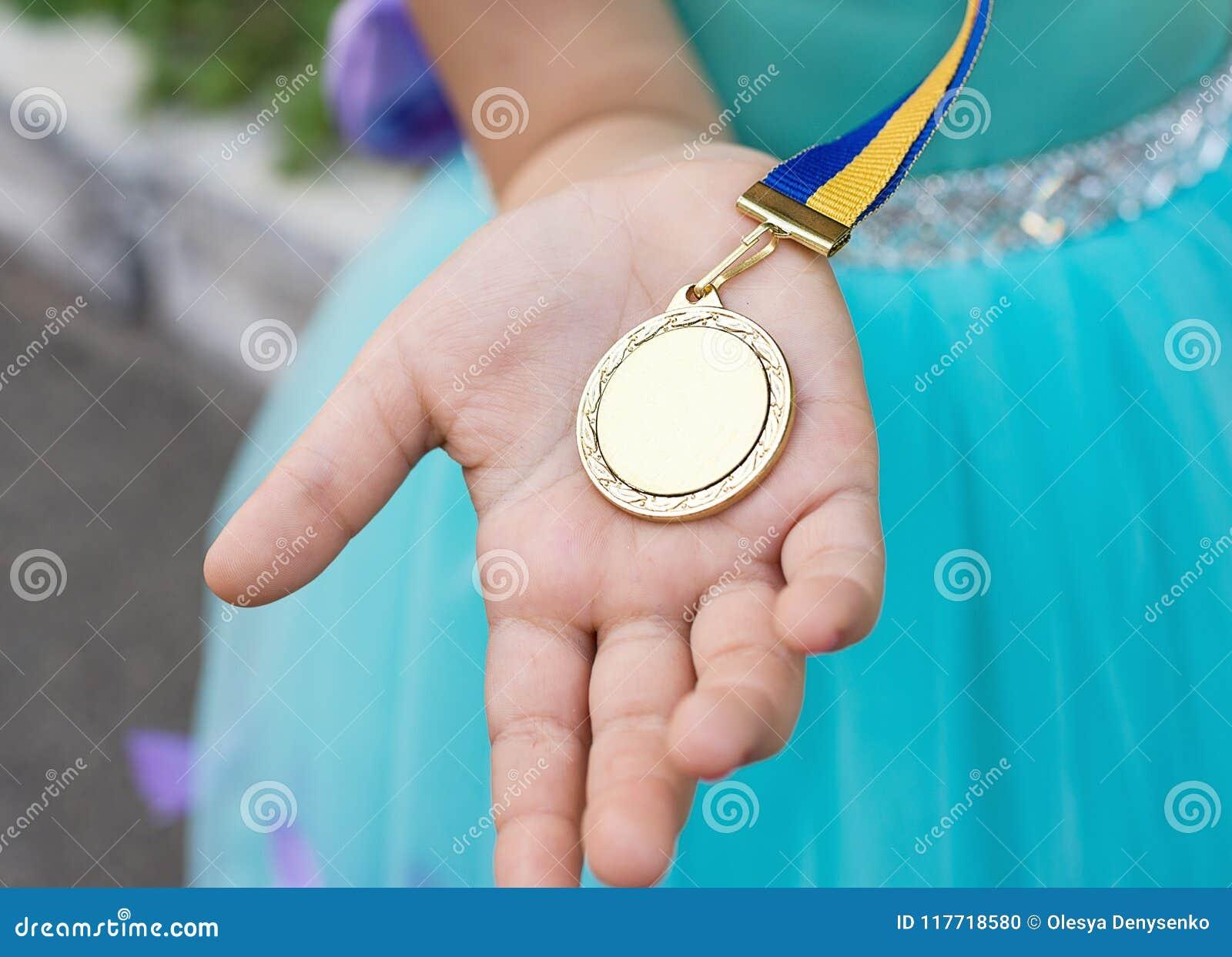 Medalha de ouro na mão da menina Graduado do jardim mais amável