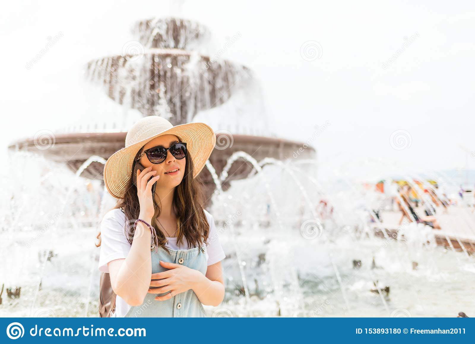 Mededeling Mooie jonge vrouw die in een hoed en glazen de telefoon uitnodigen Er is een fontein op de achtergrond