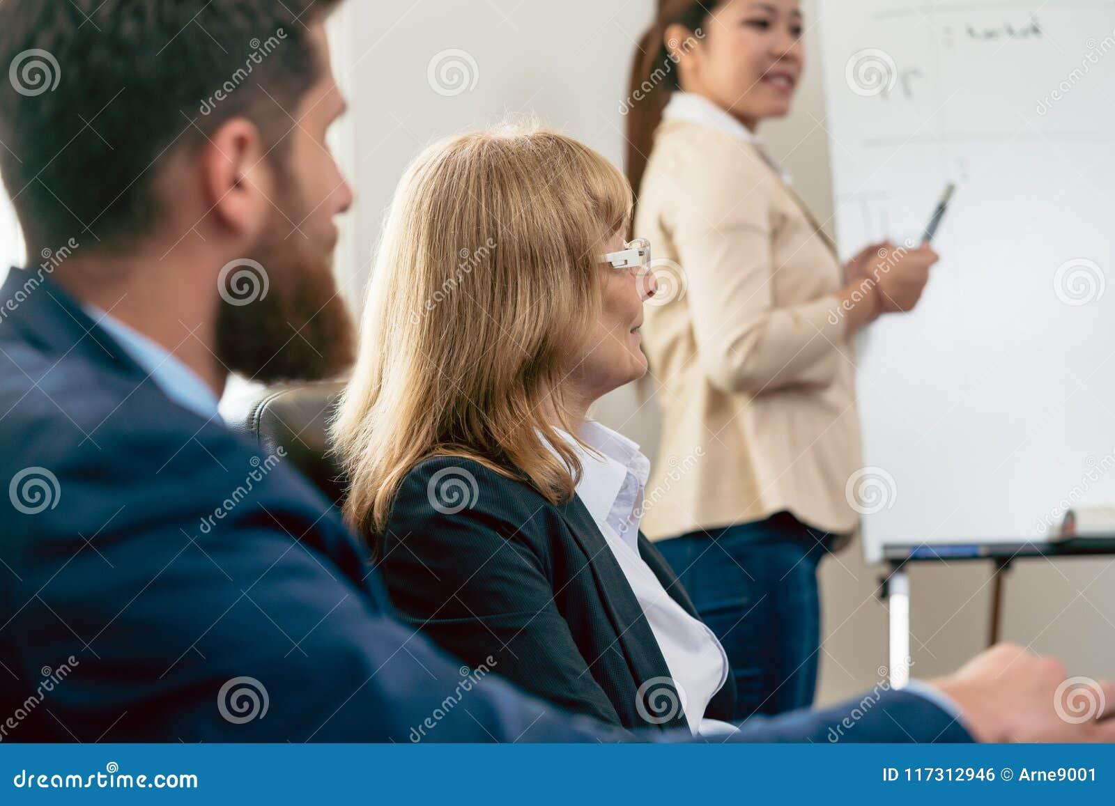 Medelålders affärskvinna som framlägger hennes åsikt under ett möte