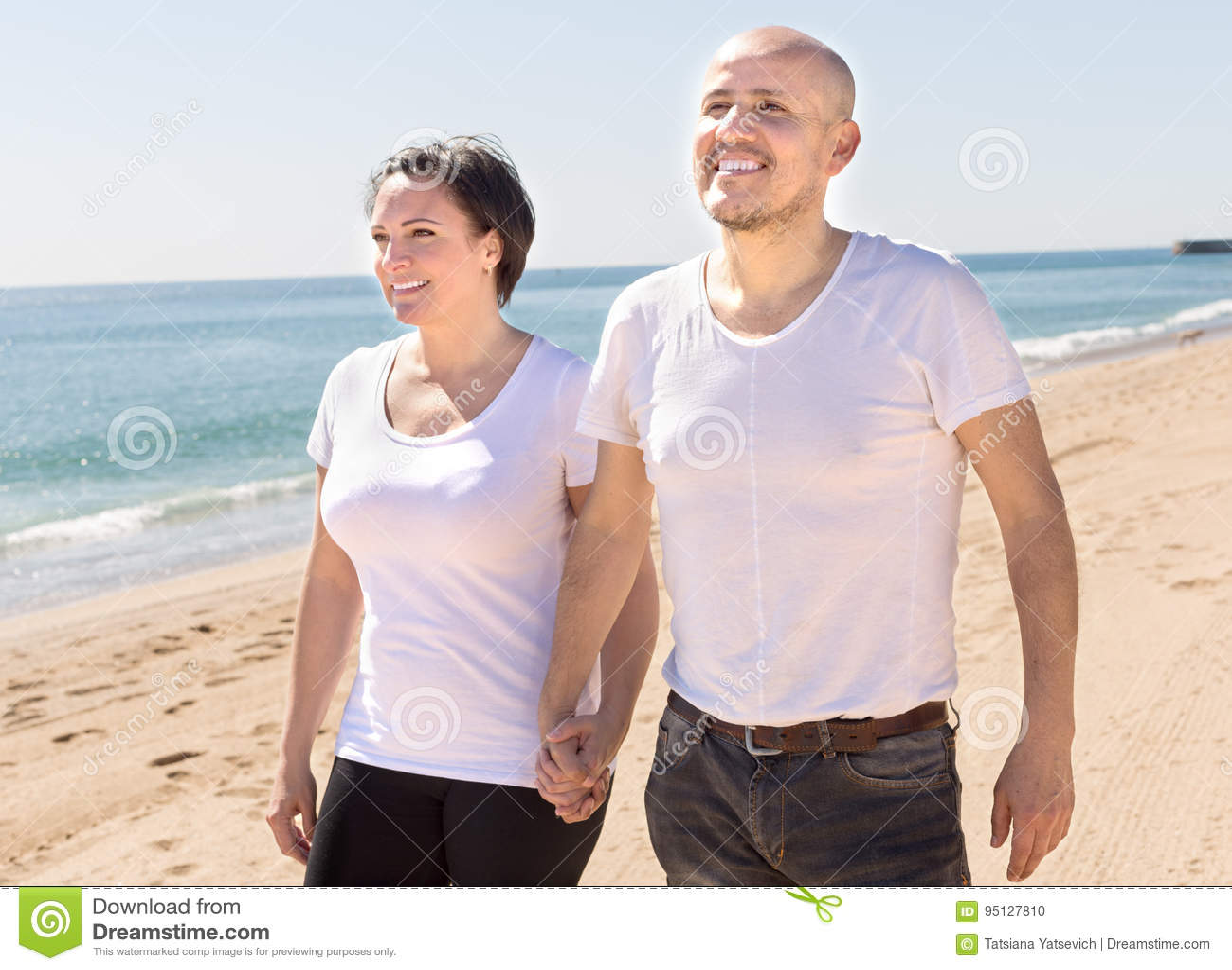 Medelålders man och kvinna i den vita T-tröja som går på stranden