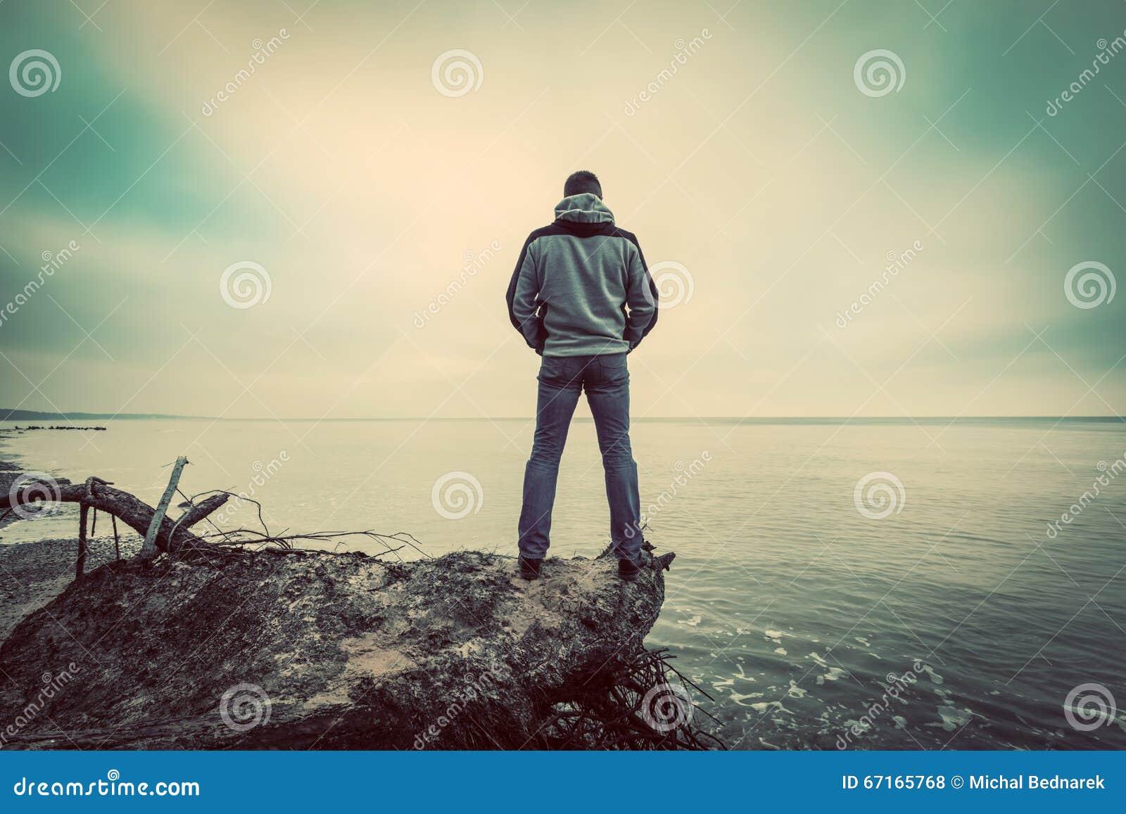 Medelålderst mananseende på brutet träd på den lösa stranden som ser havshorisonten