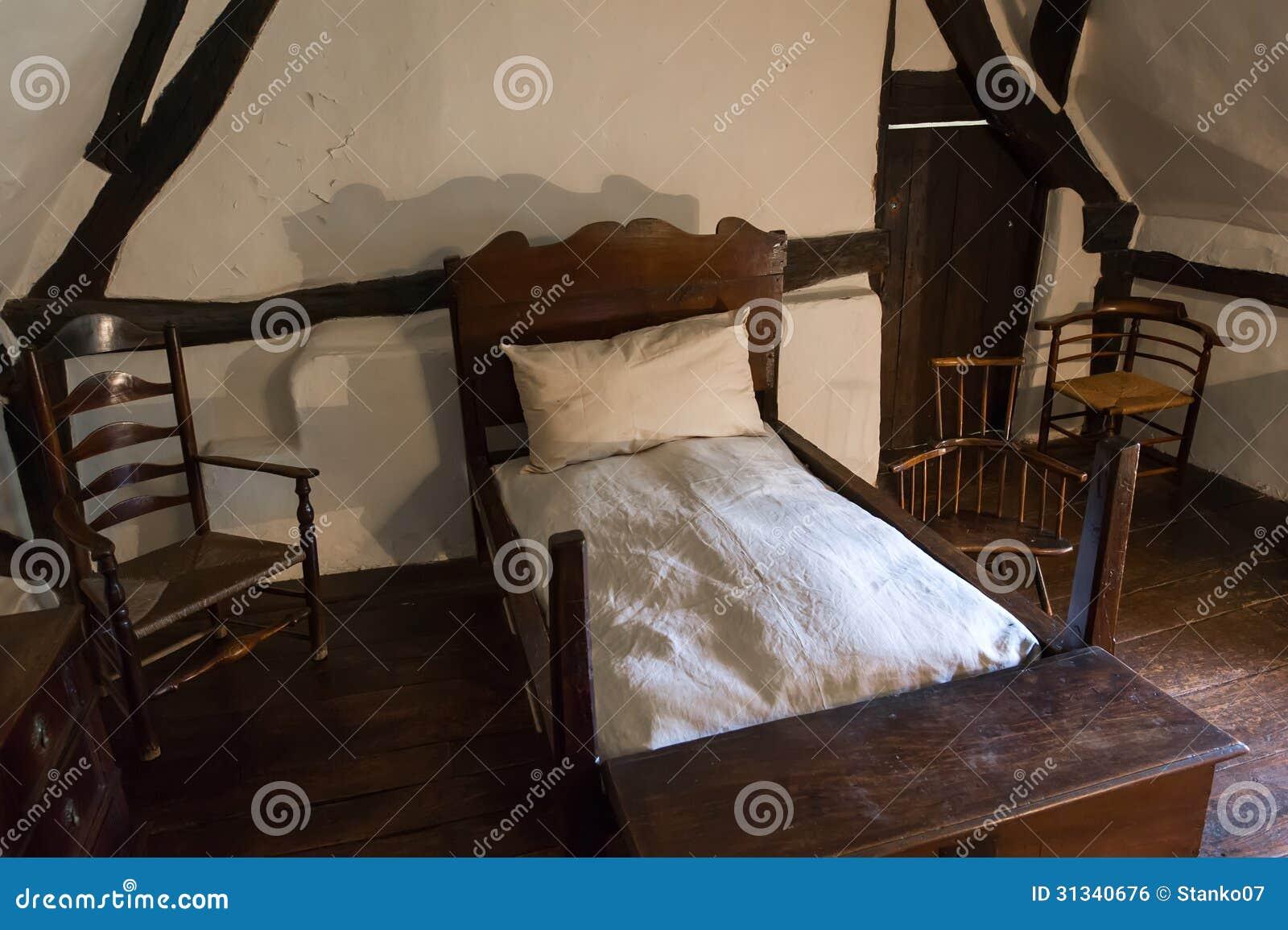 Inre av ett medeltida lantligt sovrum med det träsäng, fallet och ...