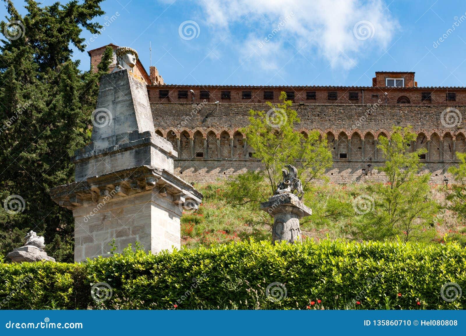 Medeltida stadsvägg med roman statyer framme, Volterra, Tuscany
