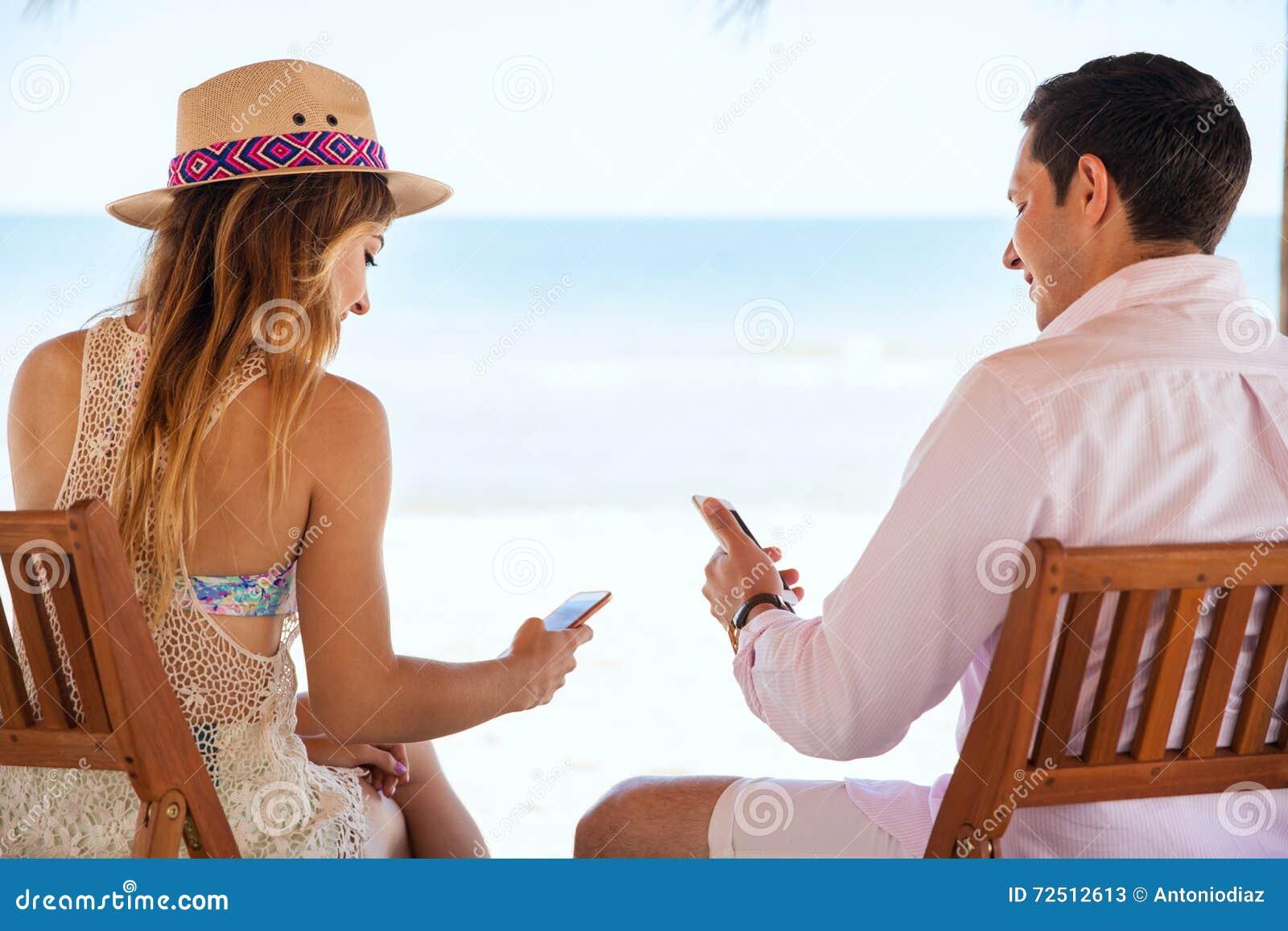 Media sociali della lettura delle coppie alla spiaggia