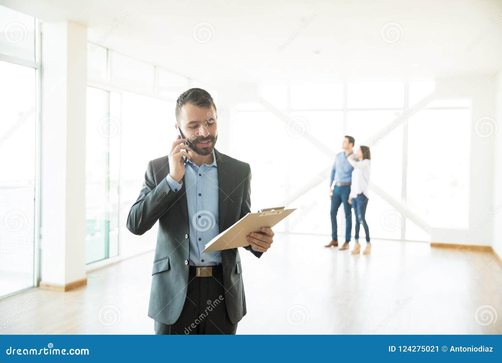 Mediador imobiliário Using Mobile Phone na casa nova