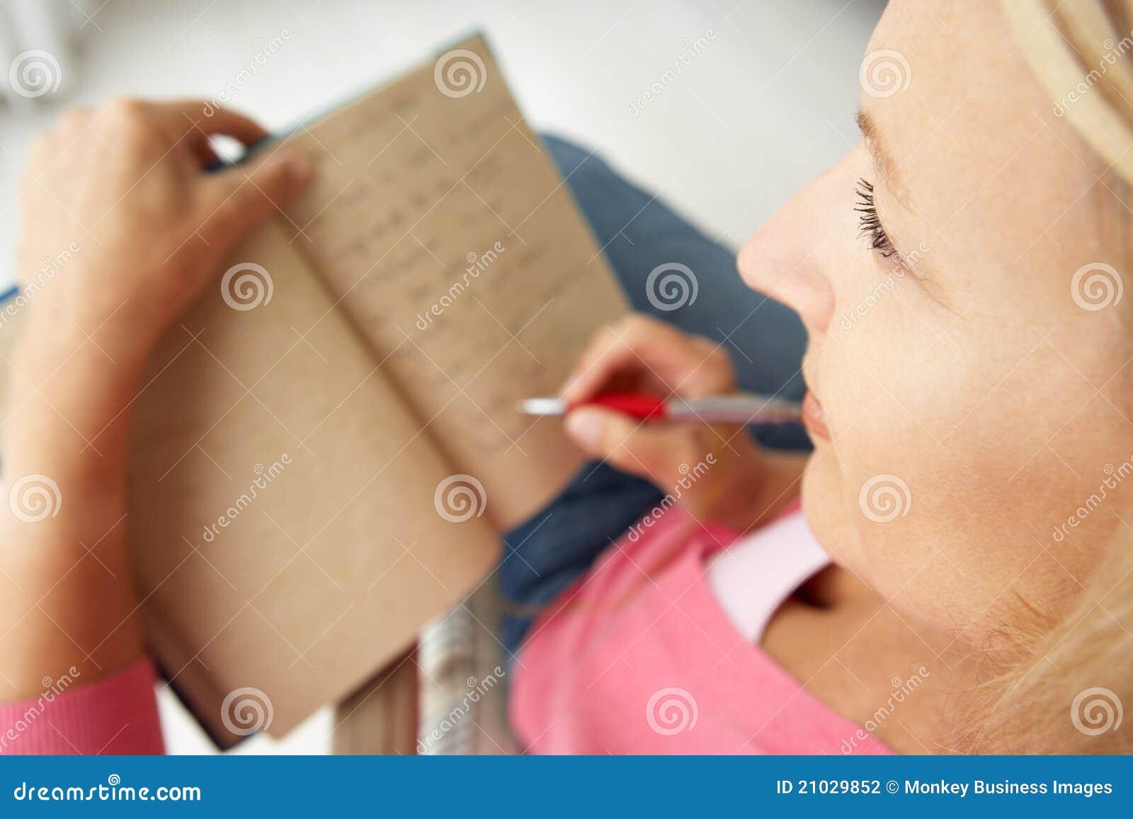 Mediados de mujeres envejecidas que escriben en cuaderno