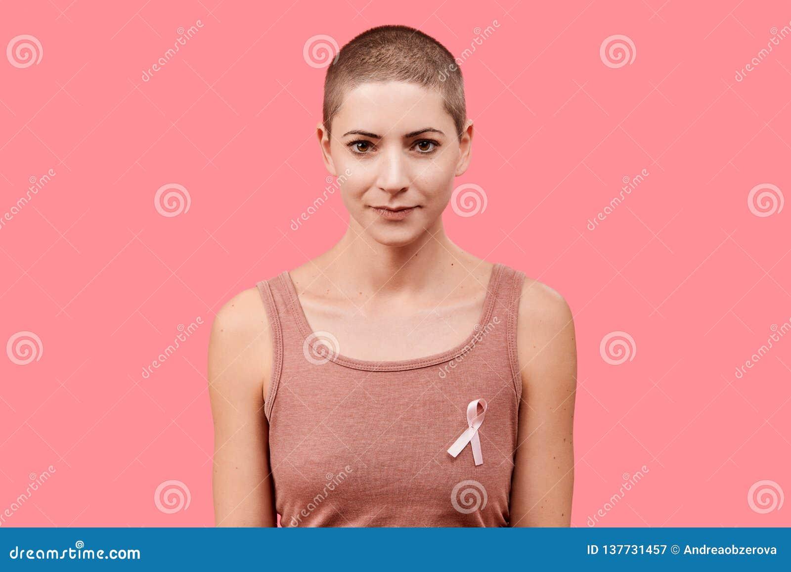 Mediados de 30s mujer sonriente, superviviente del cáncer, cinta rosada de la conciencia del cáncer de pecho que lleva, aislada s