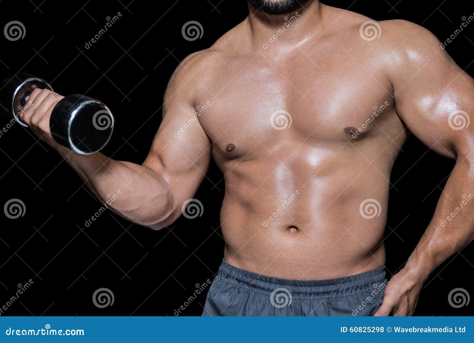 Mediados de sección de un culturista con pesa de gimnasia