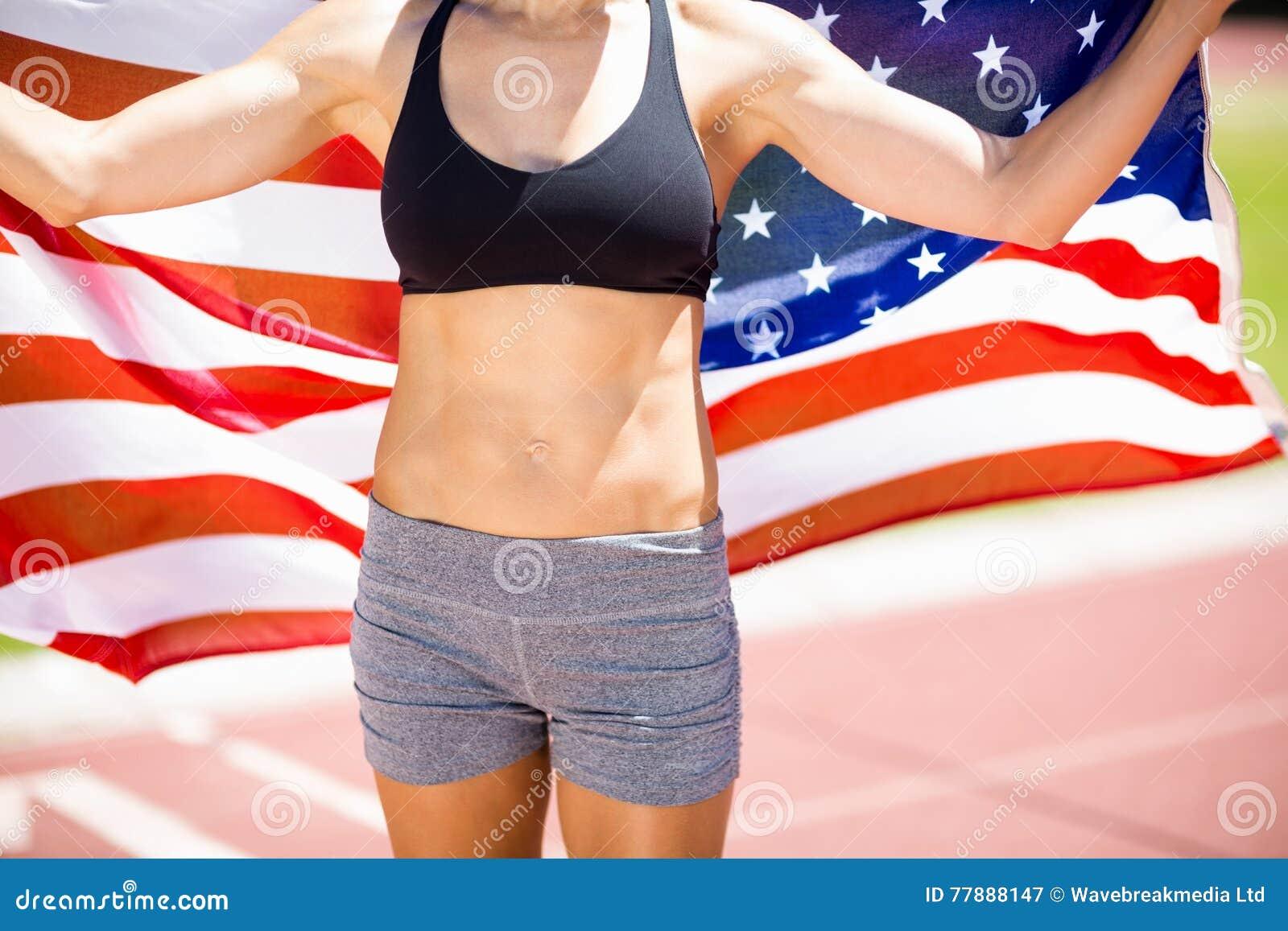 Mediados De Sección Del Atleta De Sexo Femenino Que Soporta La Bandera Americana En Pista Corriente Foto de archivo