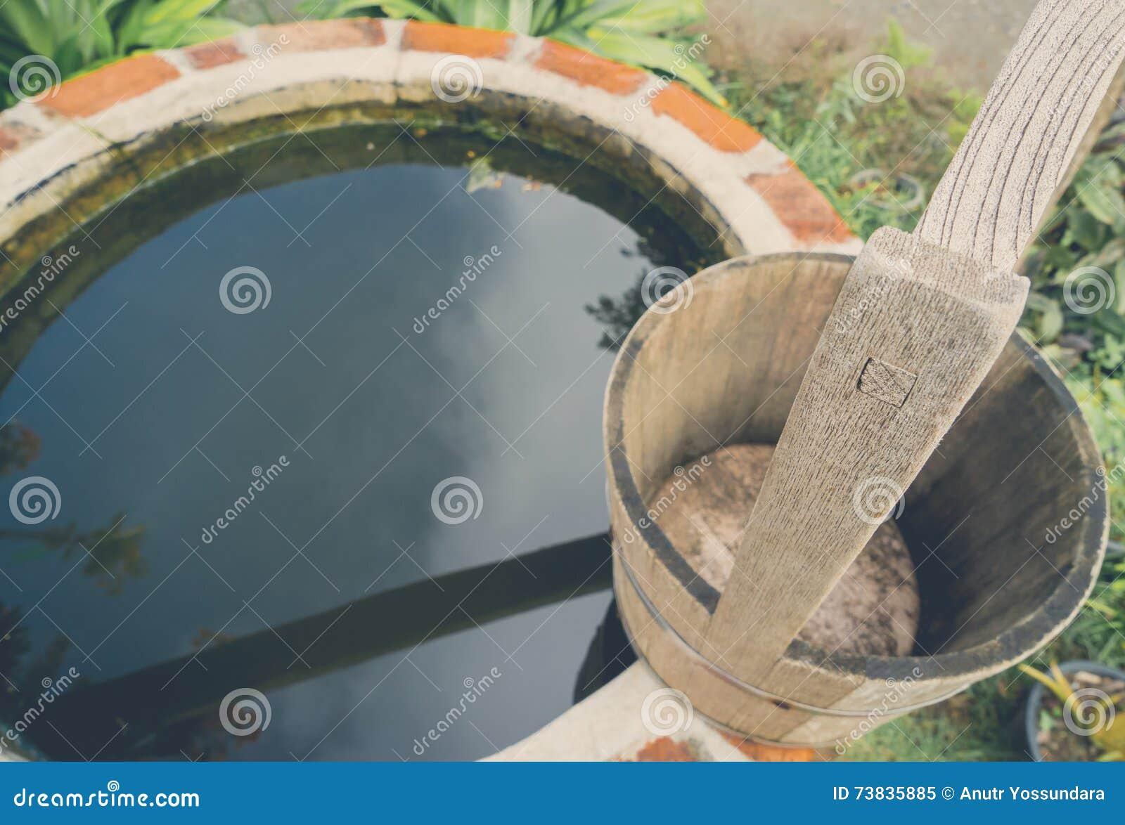 A medias alrededor del agua del ladrillo bien con el cubo de madera