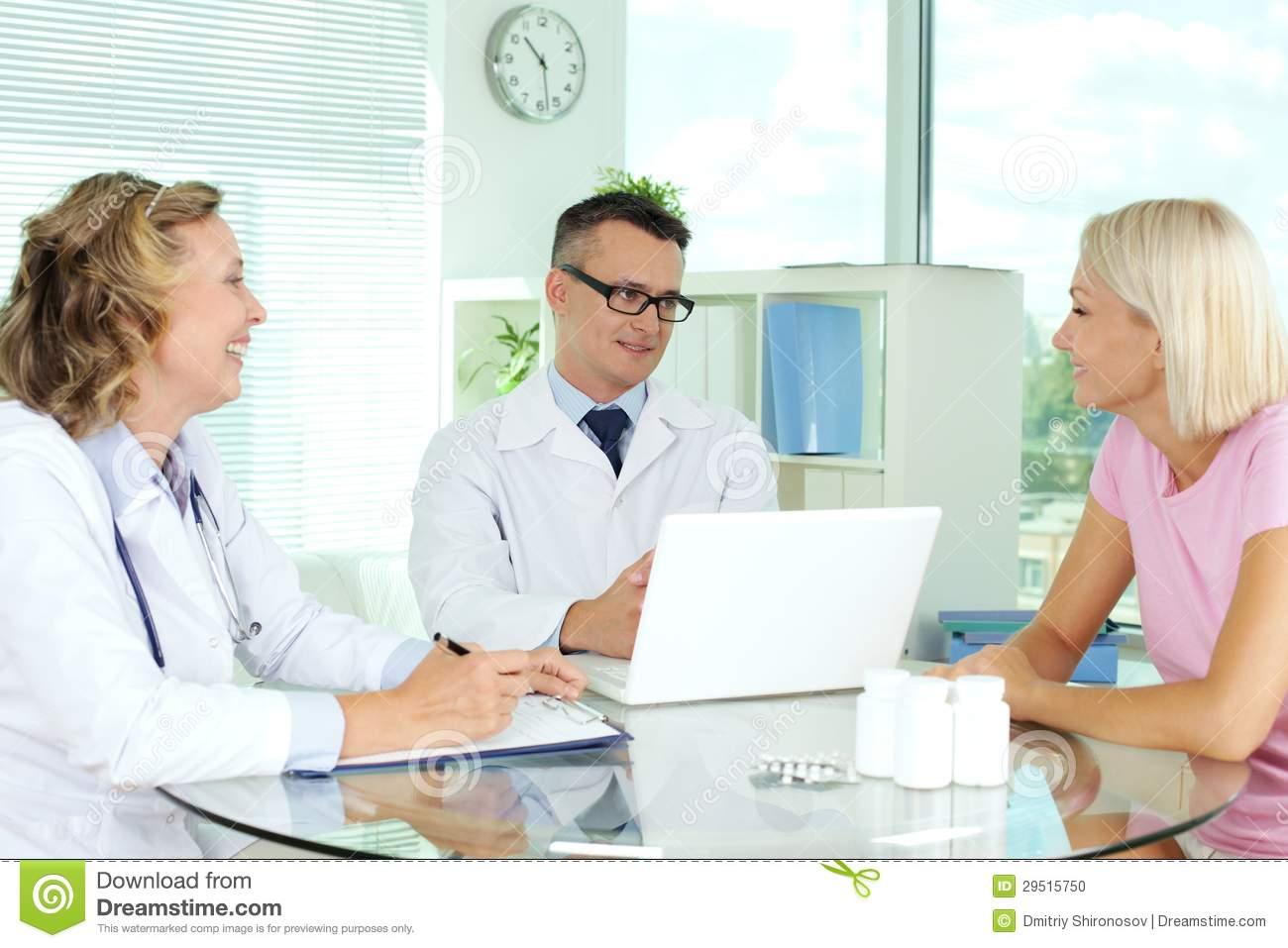 Doctors interacting with patient at medical consultation.