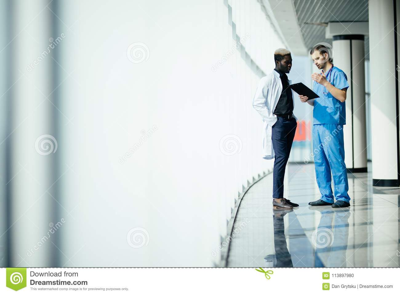 Medical multiethnic staff having discussion in a hospital hallway. Two doctors working in a medical clinic. Two hospital workers d