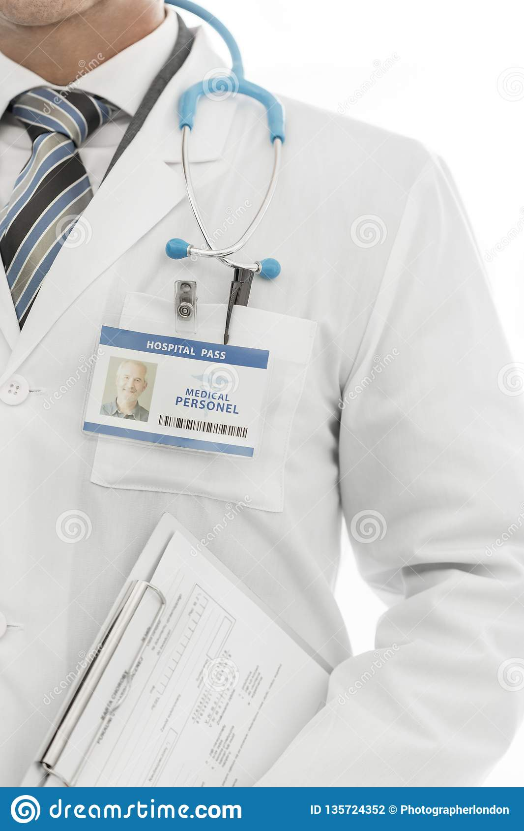 Midsection of doctor in labcoat with identity card holding clipboard at clinic