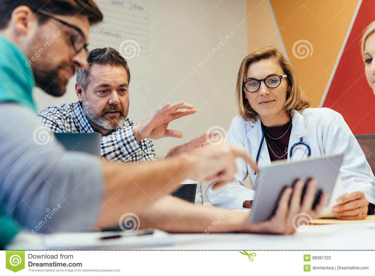 Medical staff during morning briefing in boardroom
