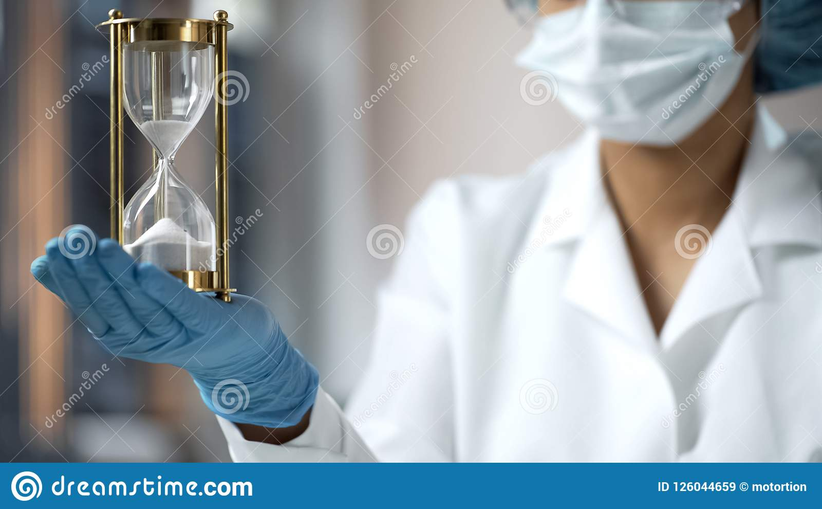 Medical worker holding sand hourglass on palm, terminal disease, life expiring