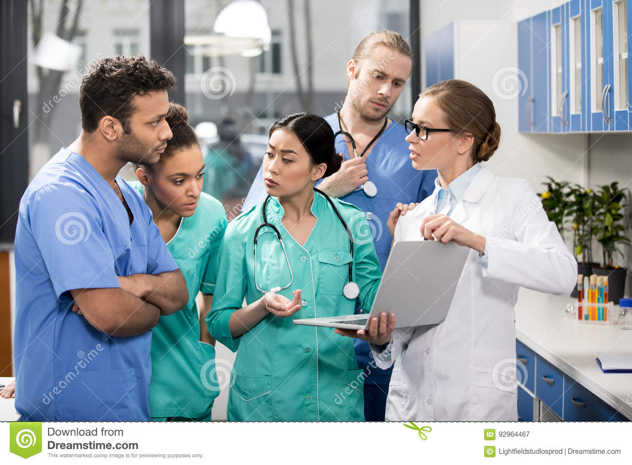 Medical workers using laptop during discussion in lab