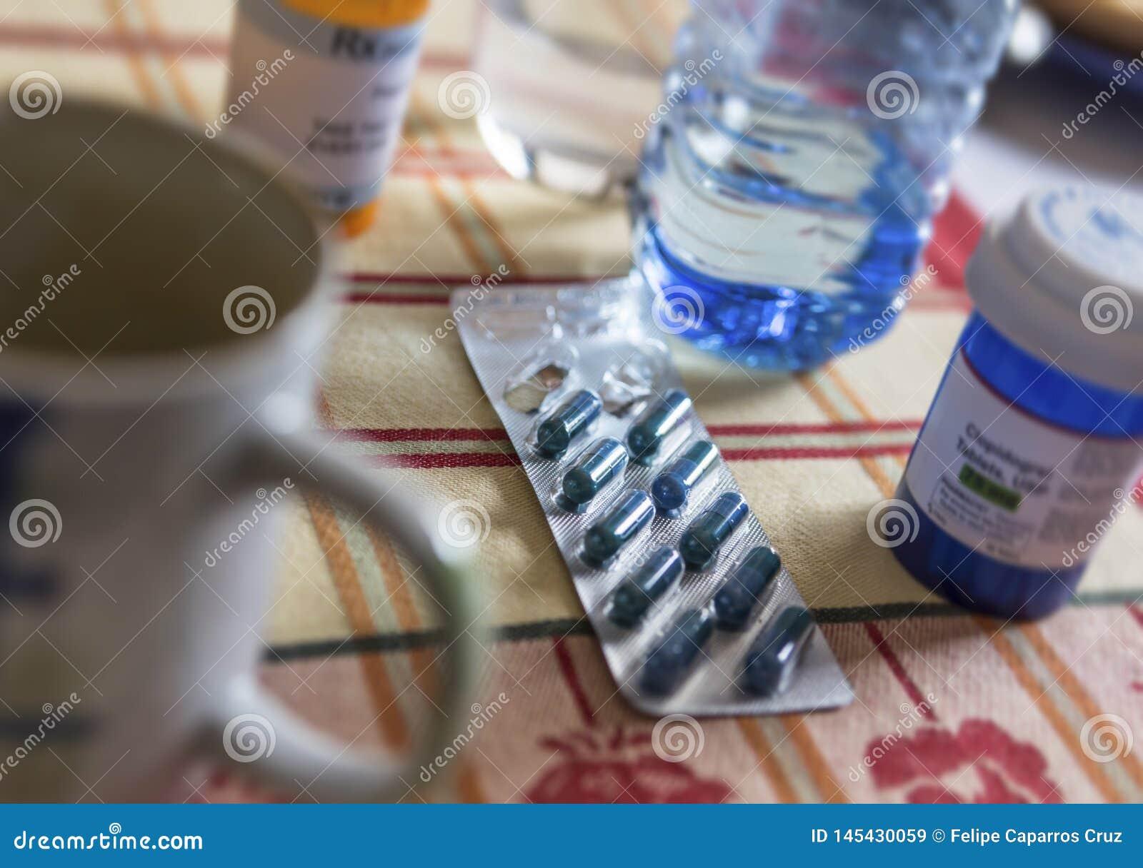 Medicamenta??o durante o caf? da manh?, c?psulas ao lado de um vidro da ?gua