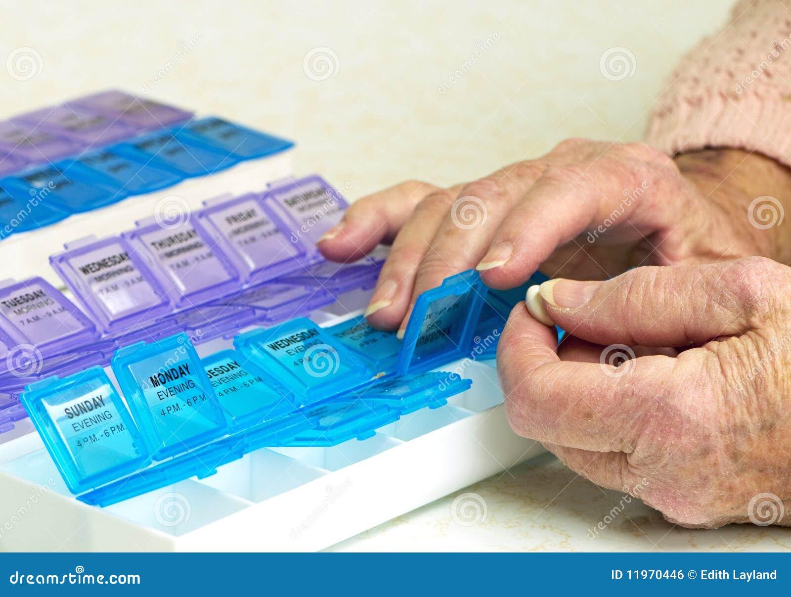 Medicamentos de venta com receita no organizador com mãos idosas