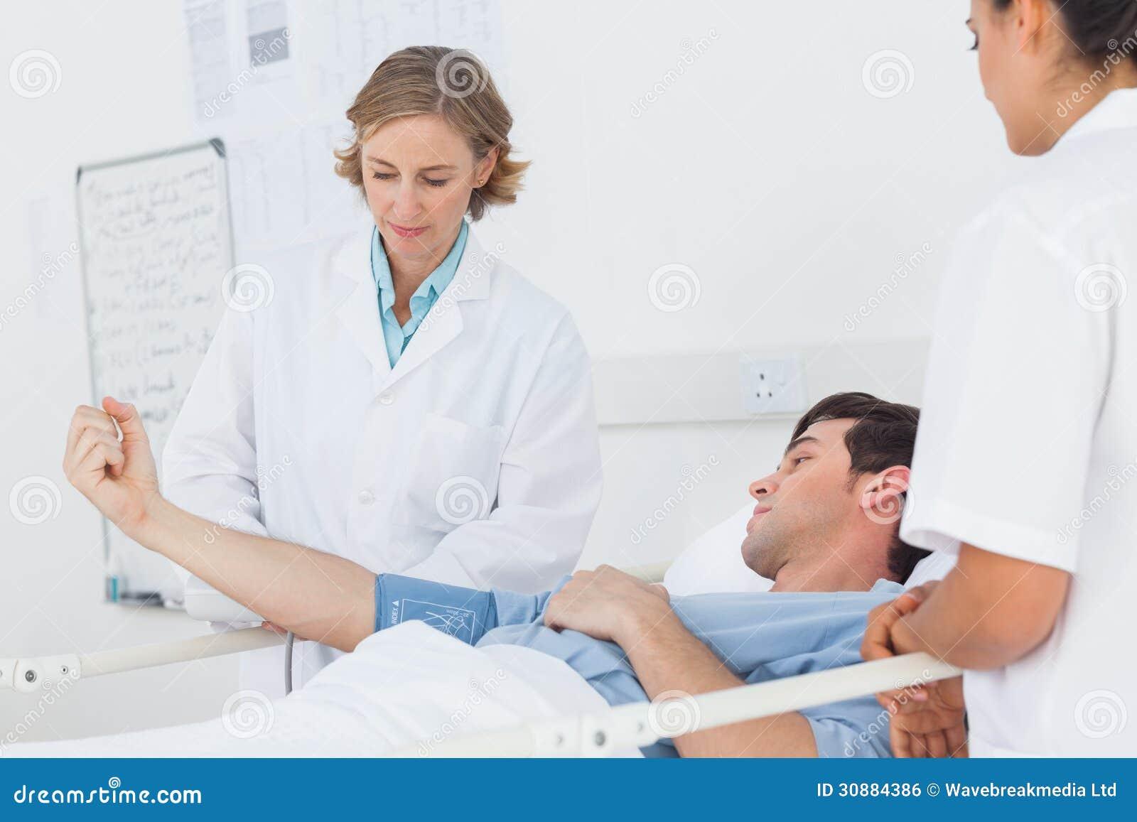 Medici che misurano la pressione sanguigna di un paziente maschio