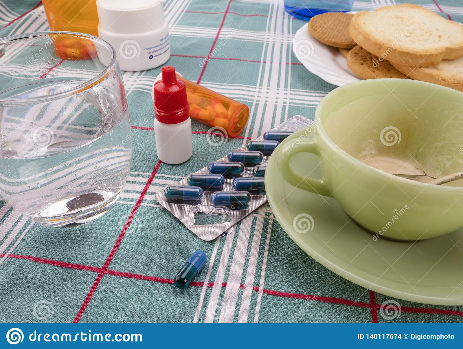 Medicijn tijdens ontbijt, capsules naast een glas water, conceptueel beeld