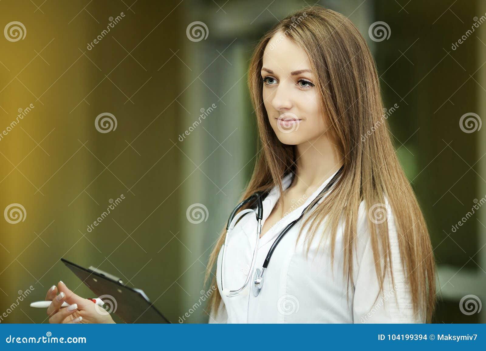 Medicin Stående av en le barnsjuksköterska med en suddig patient i sjukhuskorridoren Kyla kläder doktor Familjdoktor