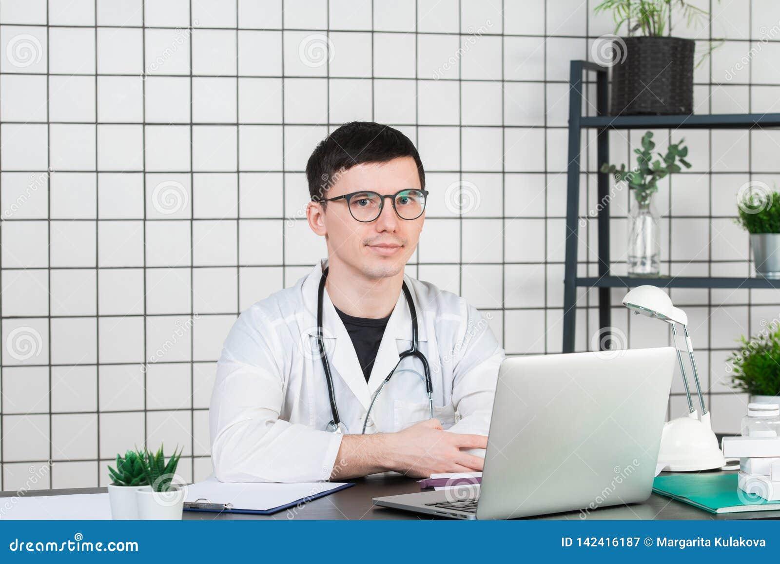 Medicina, profissão, tecnologia e conceito dos povos - doutor masculino de sorriso com o portátil no escritório médico