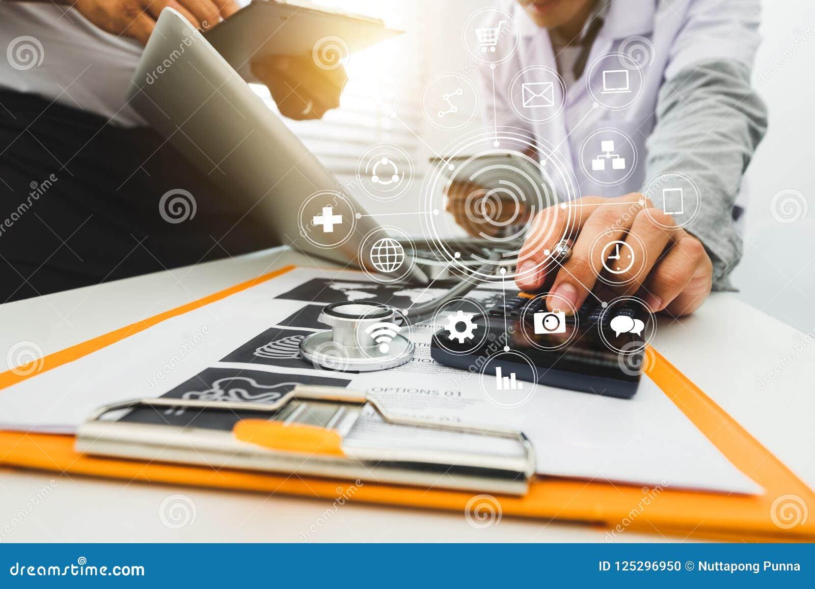 Medicindoktorshanden som arbetar med den moderna datoren och, ilar telefonen, digital minnestavla med hans lag på det vita skrivb