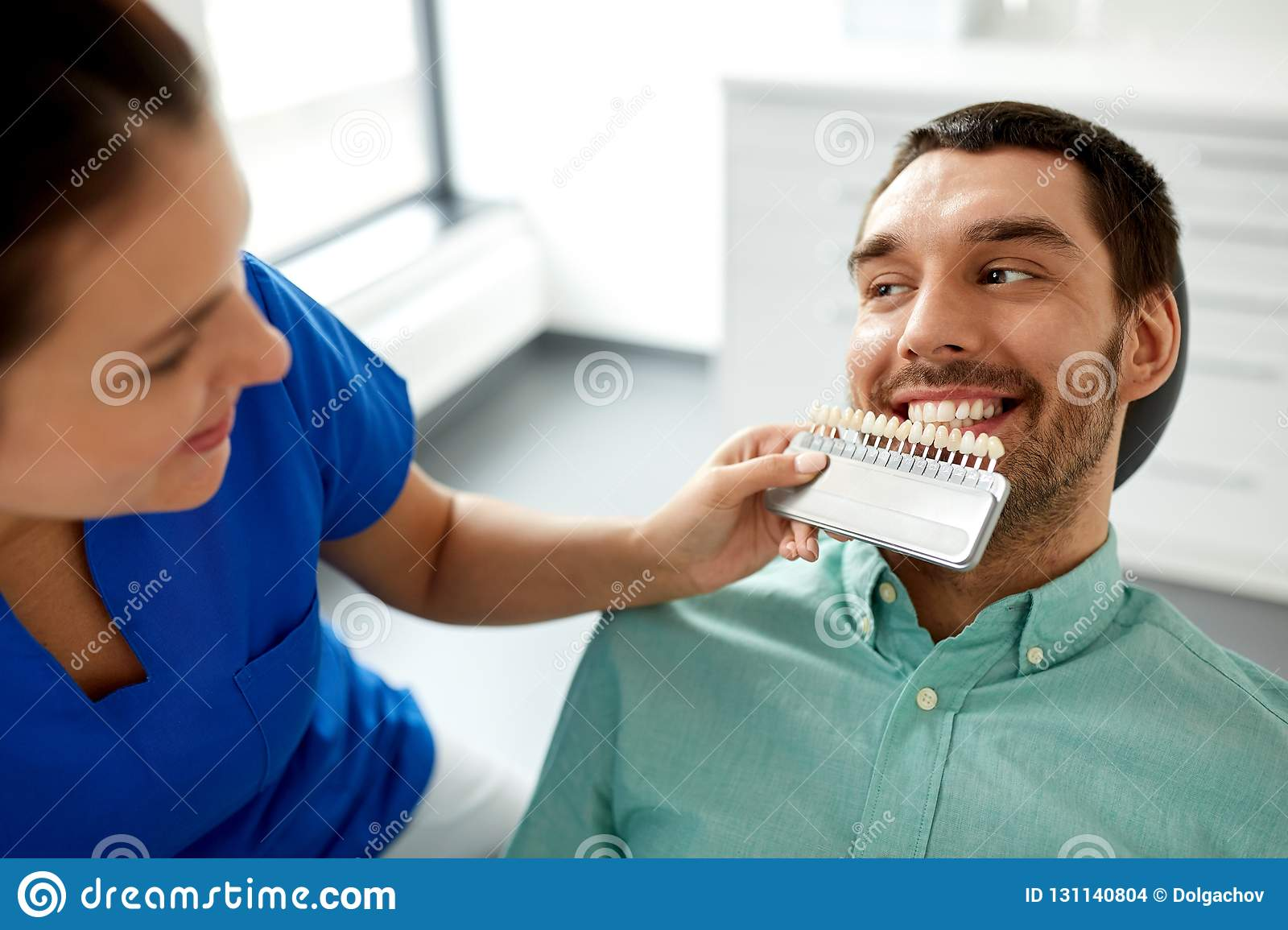 Dentist Choosing Tooth Color For Patient At Clinic Stock