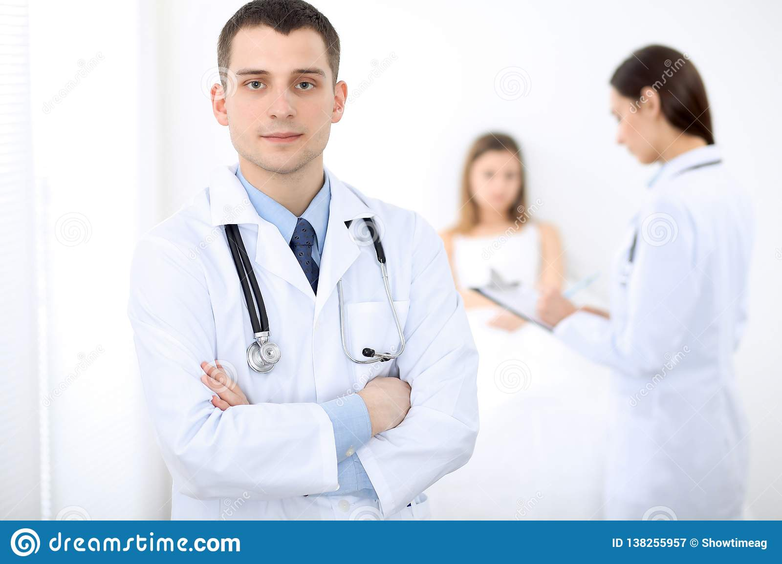 Medicine doctor standing and smiling on the background with patient in the bed