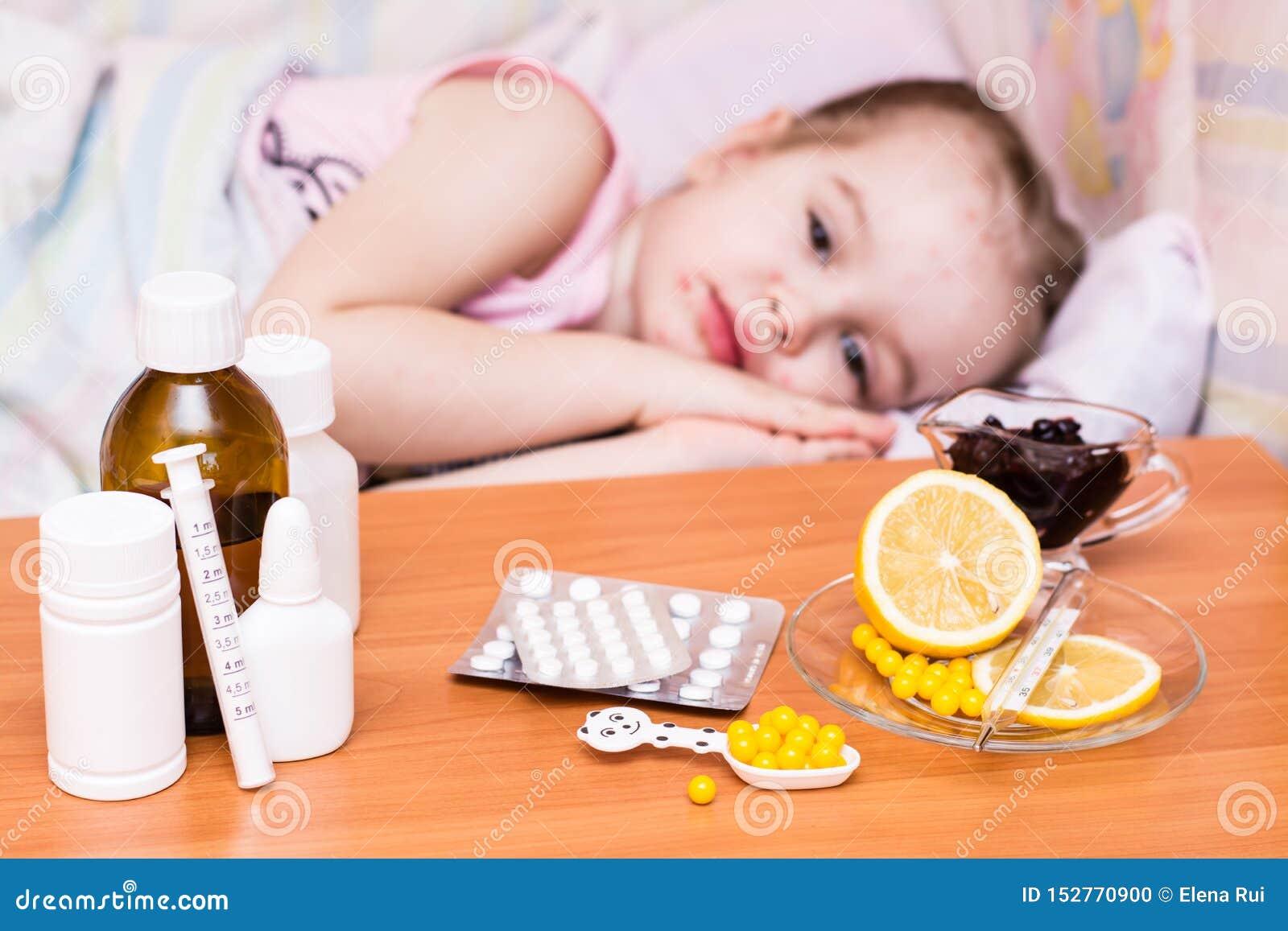 Medicine e vitamine sulla tavola contro lo sfondo di un bambino in un letto che ha varicella
